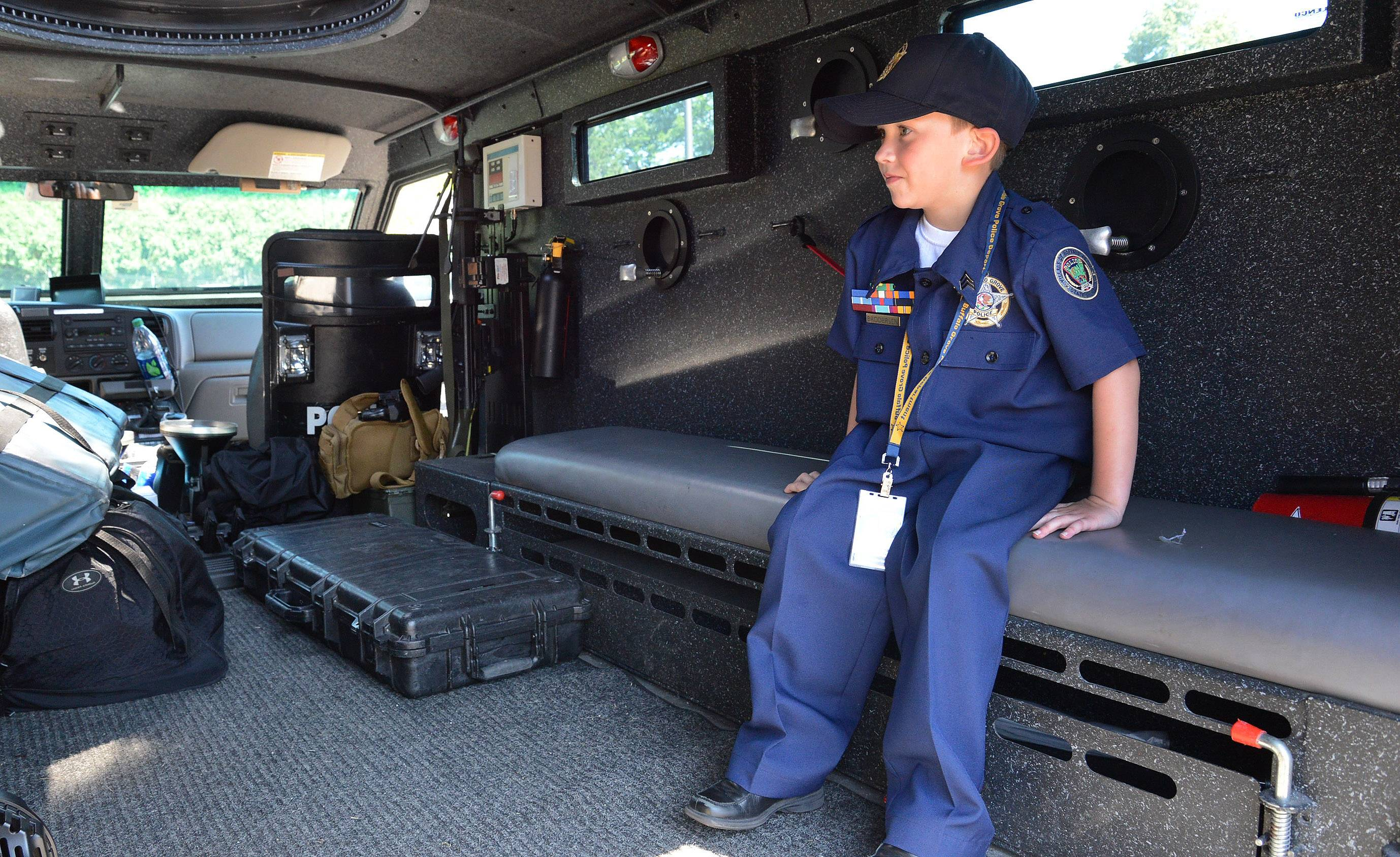 Seven-year-old Adam Brodersen, of Palatine, sits inside the NIPAS Bear Cat.