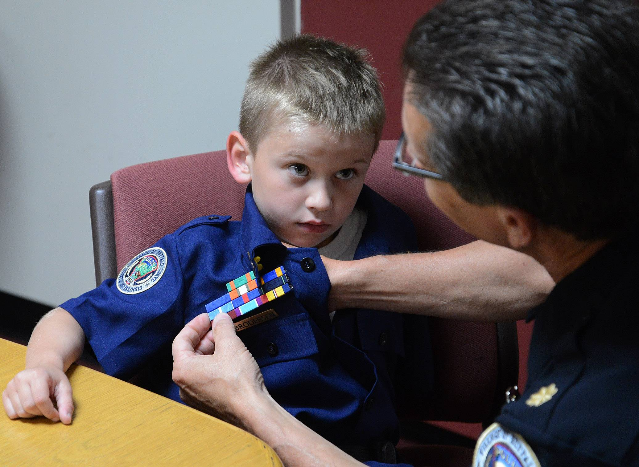 "Seven-year-old Adam Brodersen, of Palatine, gets an Award Ribbon Bar pinned on his uniform by Cmdr. Jim Newton during ""Cop For A Day"" at the Buffalo Grove police department."