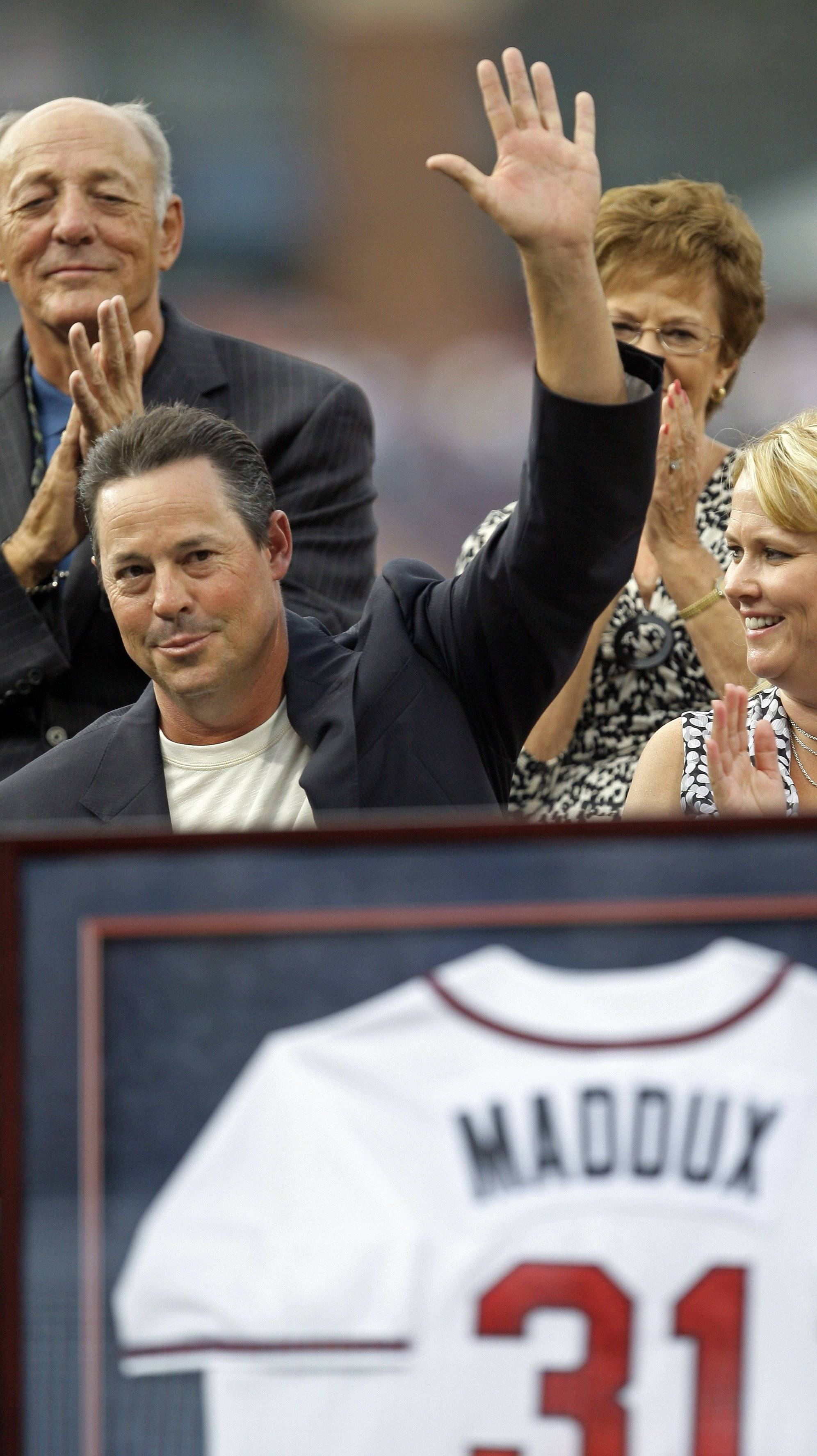 Former Atlanta Braves pitcher Greg Maddux waves to the crowd during a ceremony to retire his number 31 before a baseball game against the New York Mets in Atlanta, Friday, July, 17, 2009.