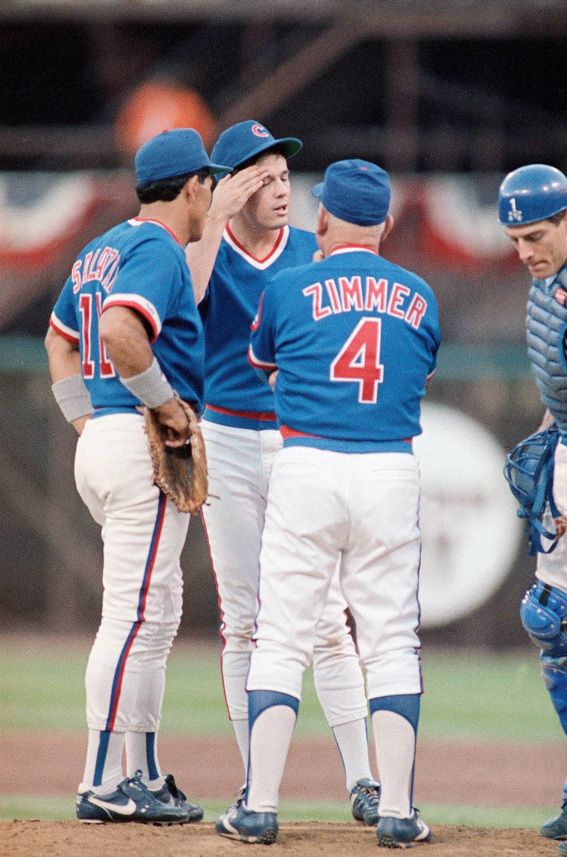 Chicago Cubs starting pitcher Greg Maddux, center, wipes his brow as he talks to Cubs third baseman Luis Salazar (11) and manager Don Zimmer (4) during the third inning of the fourth game of the NLCS against the Giants, Sunday, Oct. 8, 1989, San Francisco, Calif. Maddux was pulled from the game in the fourth inning.