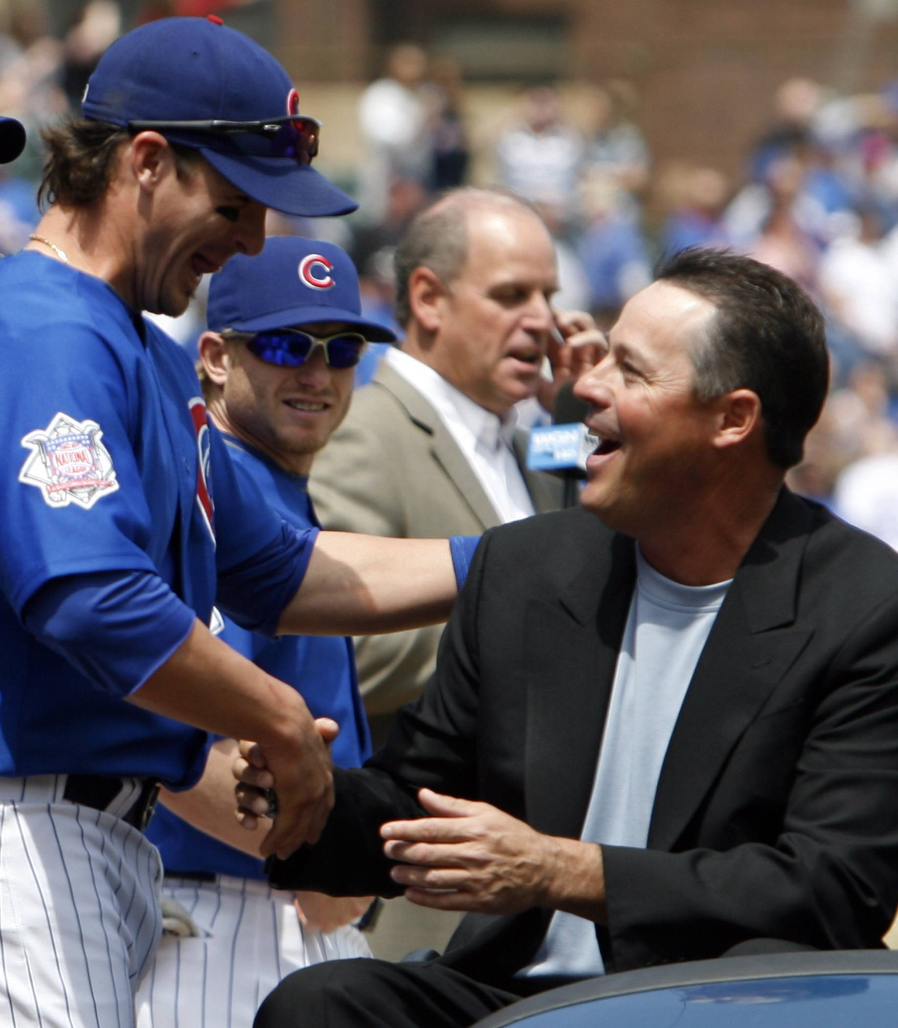 Former Chicago Cubs player Greg Maddux, right, shakes hands with Cubs' Ryan Theriot while celebrating with Ferguson Jenkins (not shown) at Wrigley Field as the Cubs retired the No. 31 both wore with the team, before the Florida Marlins and the Cubs baseball game, Sunday, May 3, 2009, in Chicago.
