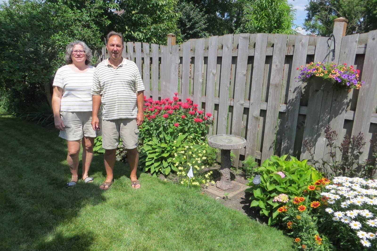 Des Plaines Garden Club members Craig and Liz Zajac stand it their garden, one of six included in the club's annual garden walk held July 10.