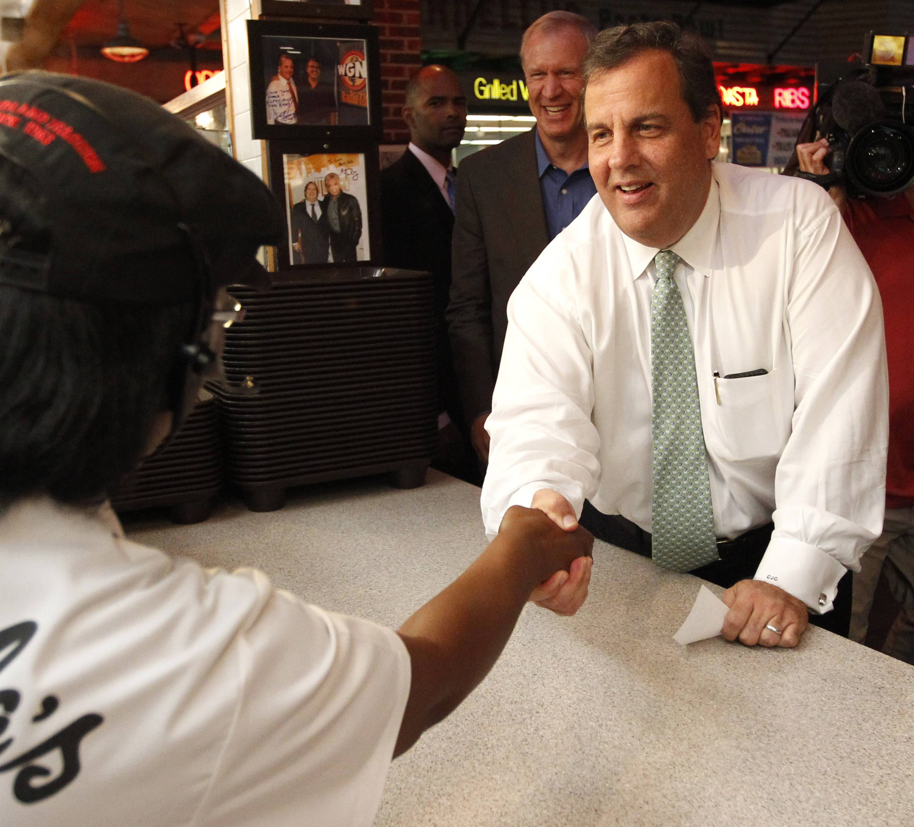 New Jersey Gov. Chris Christie, right, shakes hands at a Portillo's restaurant while Illinois Republican governor candidate Bruce Rauner watches during a campaign stop Friday in Chicago.