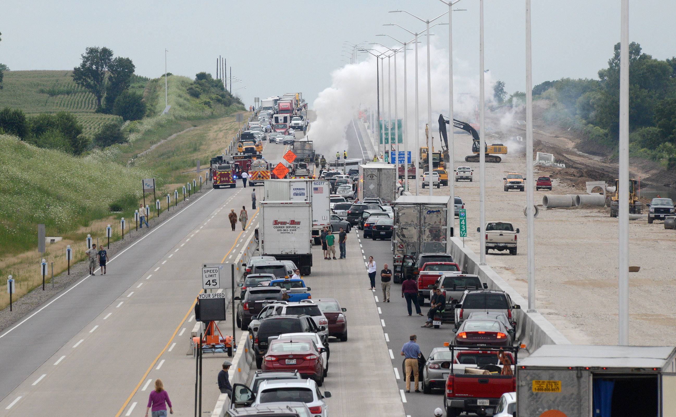 A semitrailer truck engulfed in flames causes a major traffic backup looking west on the Addams Tollway just west of the Brier Hill Road overpass.