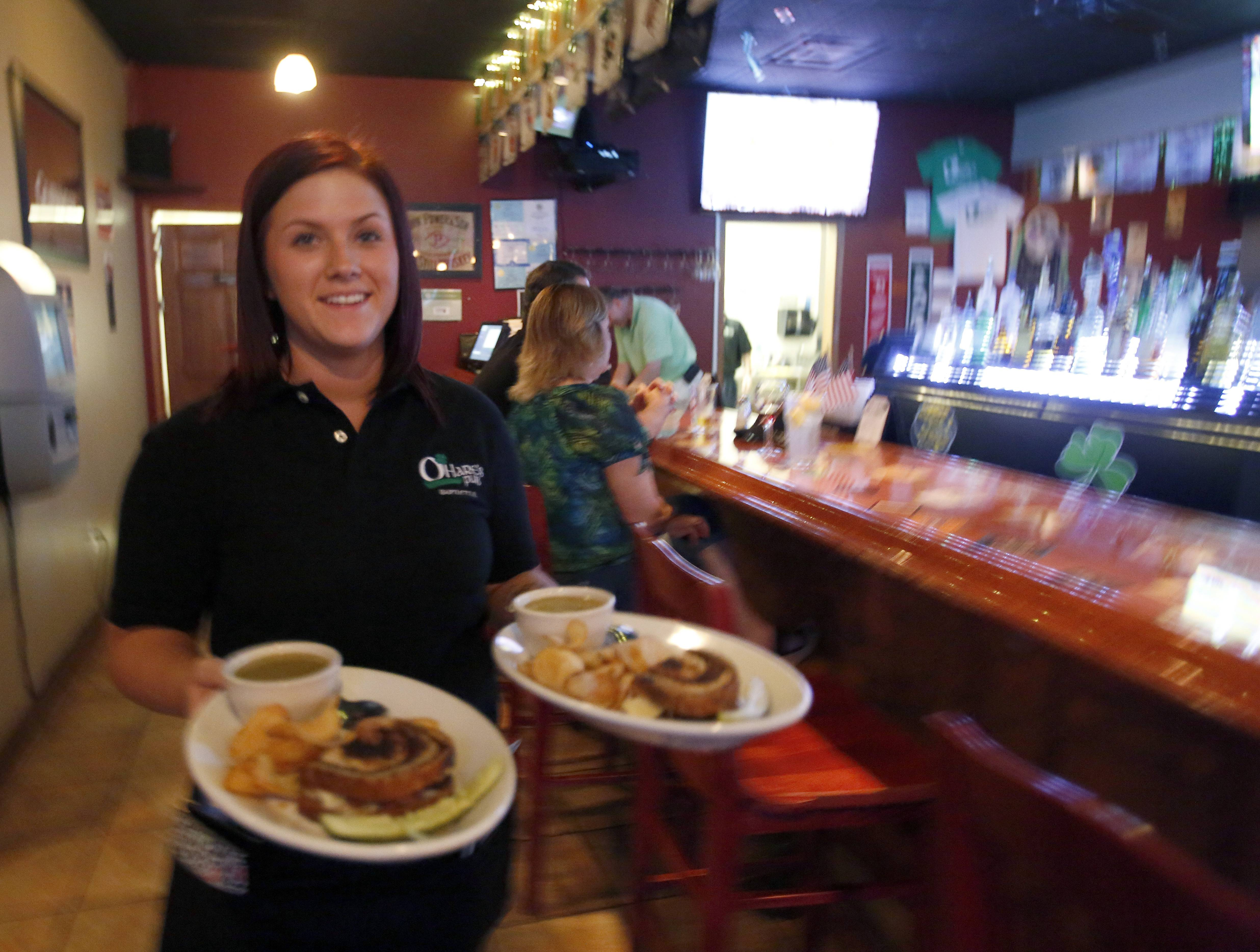Server Amanda Taylor delivers dinner to patrons at O'Hare's Pub in Bartlett.