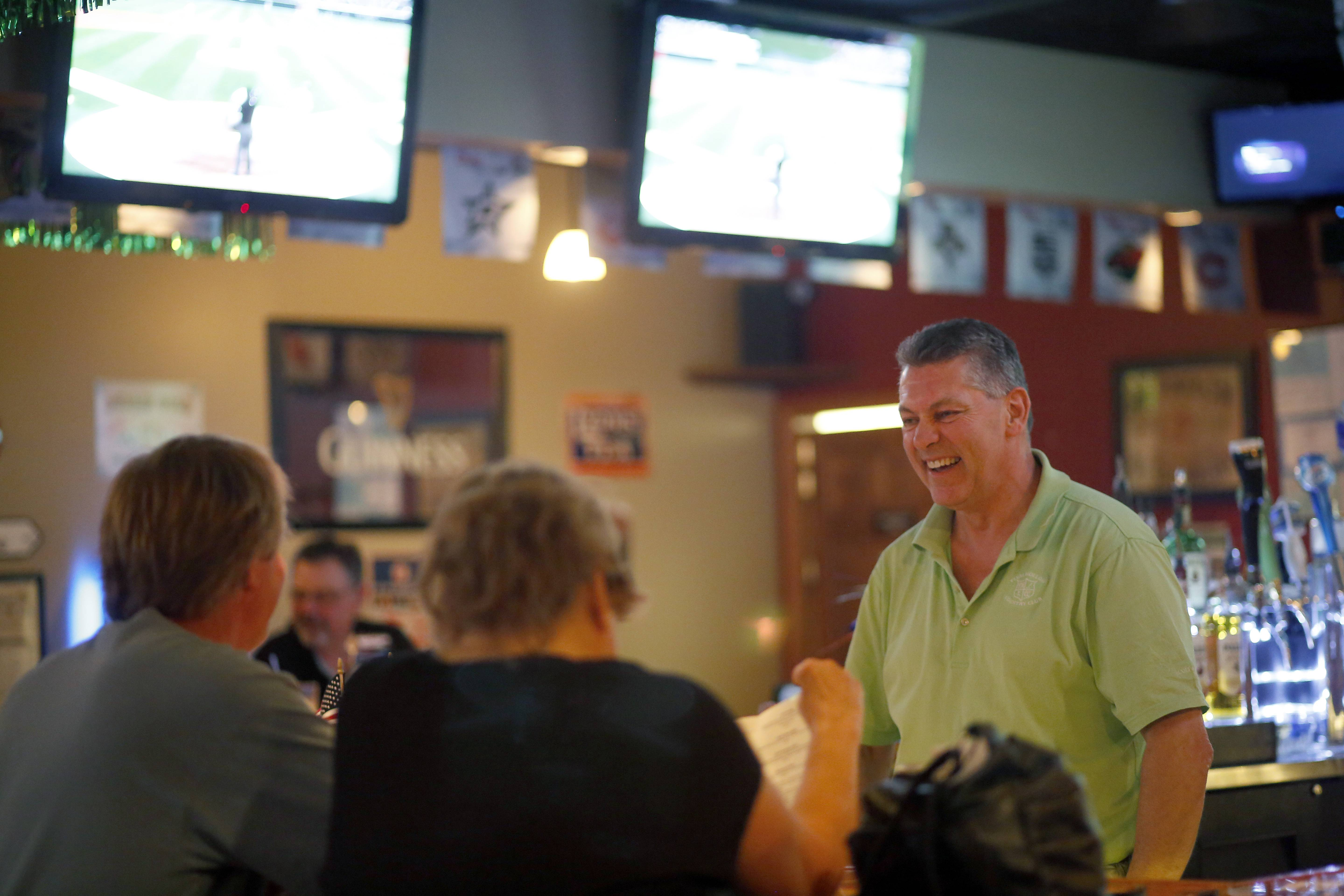 Bartender and co-owner Bill Vance chats with customers at O'Hare's Pub in Bartlett.