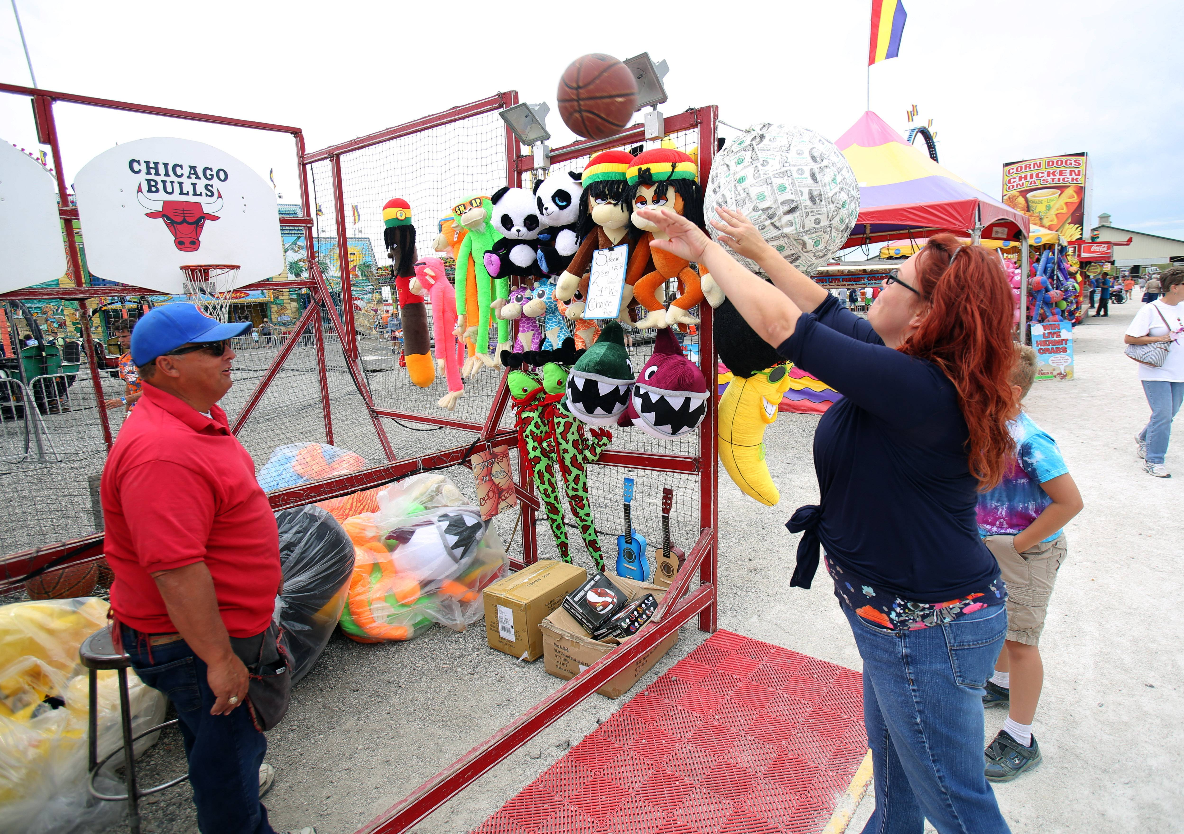 Debbie Rogers of Mundelein, right, plays a carnival game.