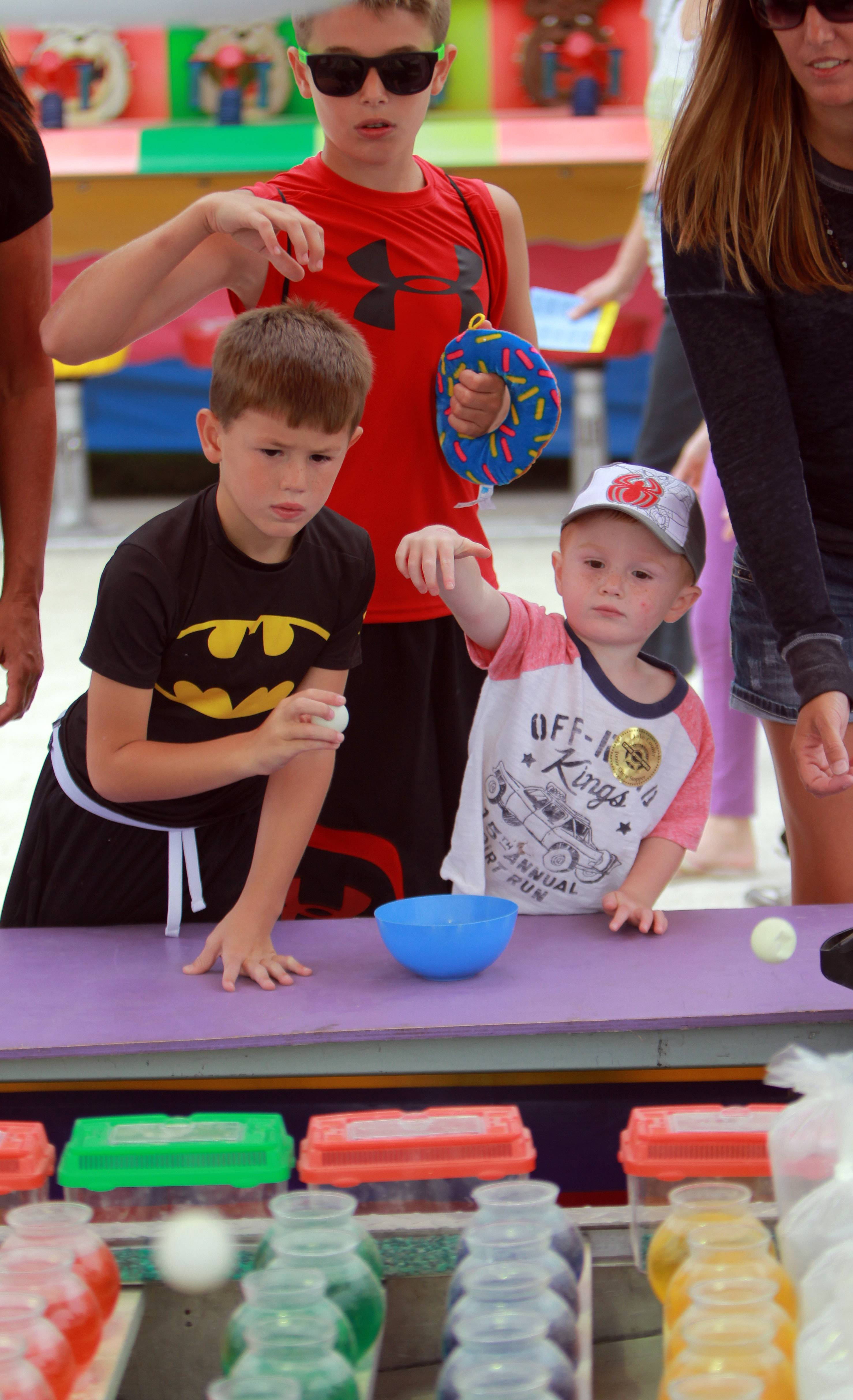 From left, brothers Jace Nelson, 5, Jacob, 10, and Jaxon, 3, all of Spring Grove, play a carnival game.