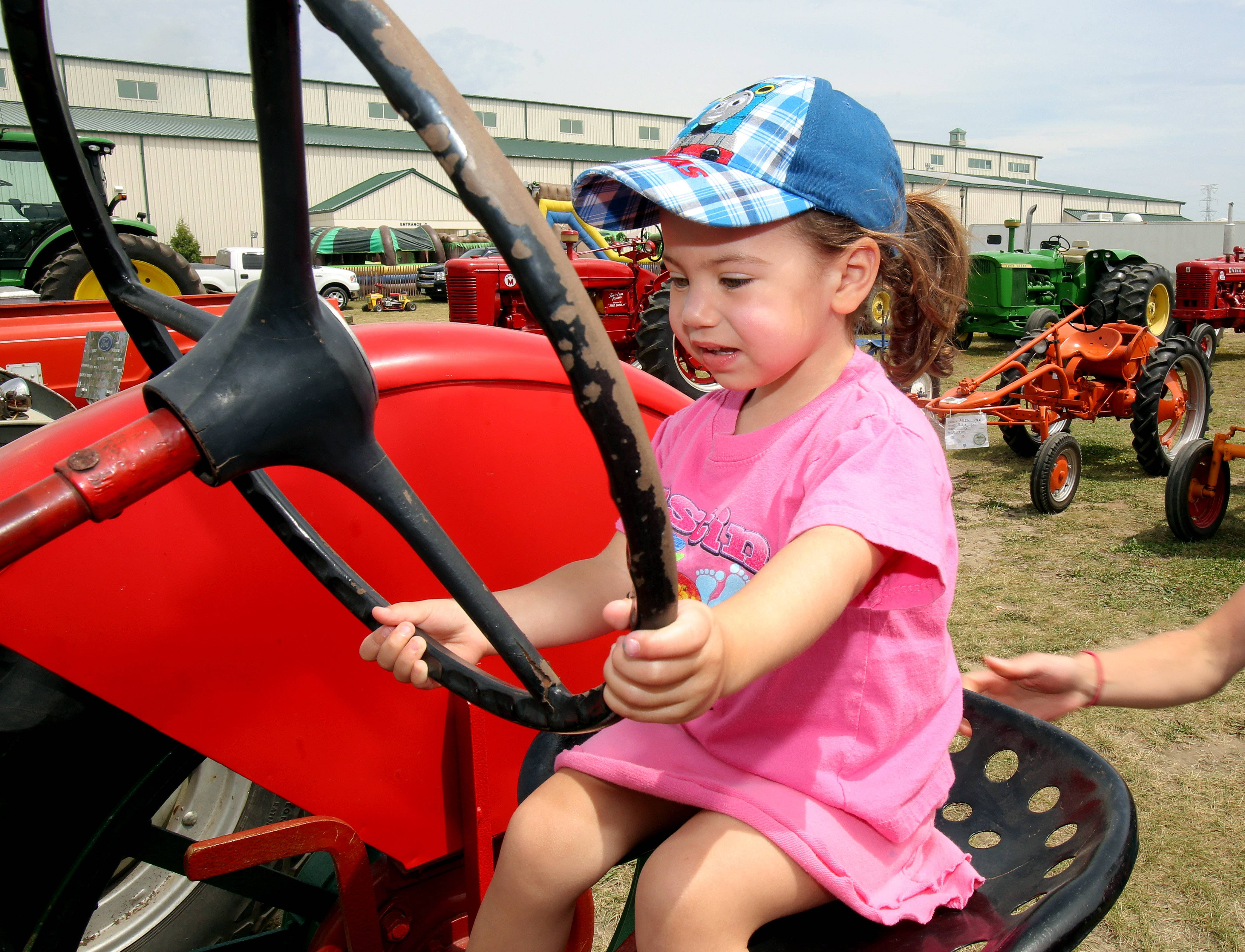 Two-year-old Georgia Roscoe of Grayslake sits behind the wheel of a tractor.