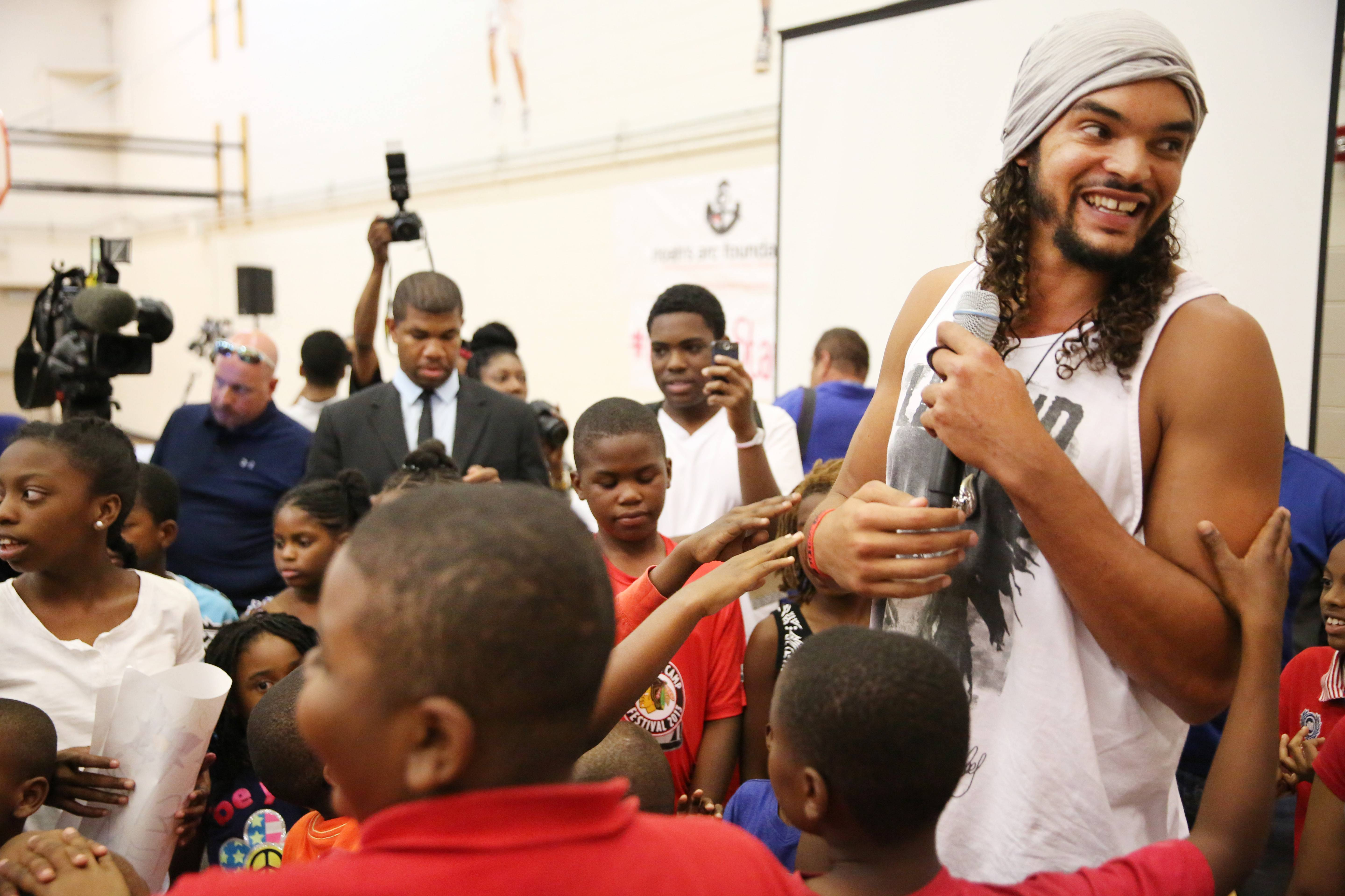 Chicago Bulls NBA All-Star Joakim Noah is surround by a group of kids as he speaks to the media about fighting gun violence in the city through his Noahs Arc Foundation, at Major Adams Community Center on Friday, July 25, 2014 in Chicago. Noah has unveiled an effort to tamp down the city's gun violence, including a public service announcement in which he stars.