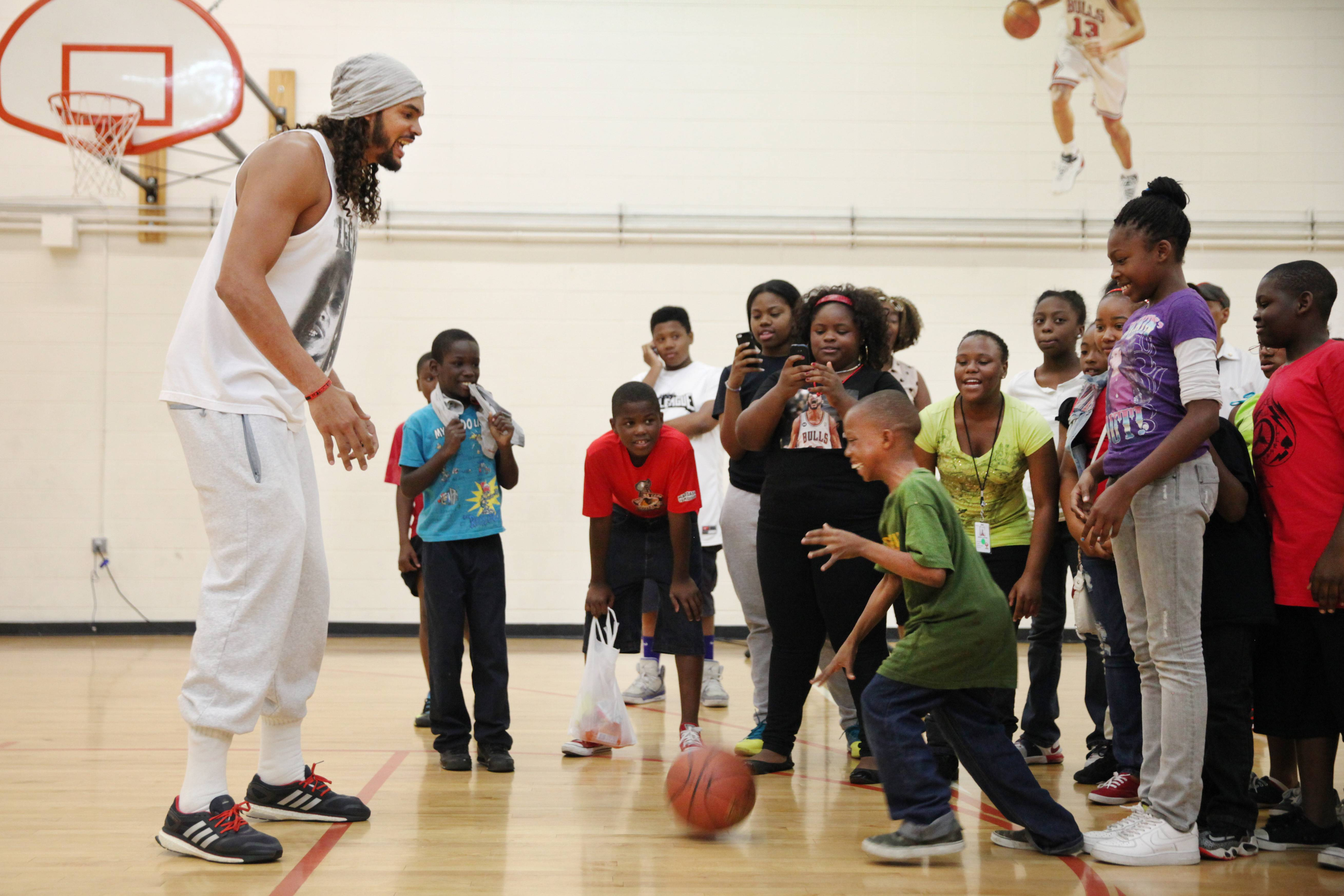 Chicago Bulls NBA All-Star Joakim Noah plays basketball with kids after speaking to the media about fighting gun violence in the city through his Noahs Arc Foundation, at Major Adams Community Center on Friday, July 25, 2014 in Chicago. Noah has unveiled an effort to tamp down the city's gun violence, including a public service announcement in which he stars.