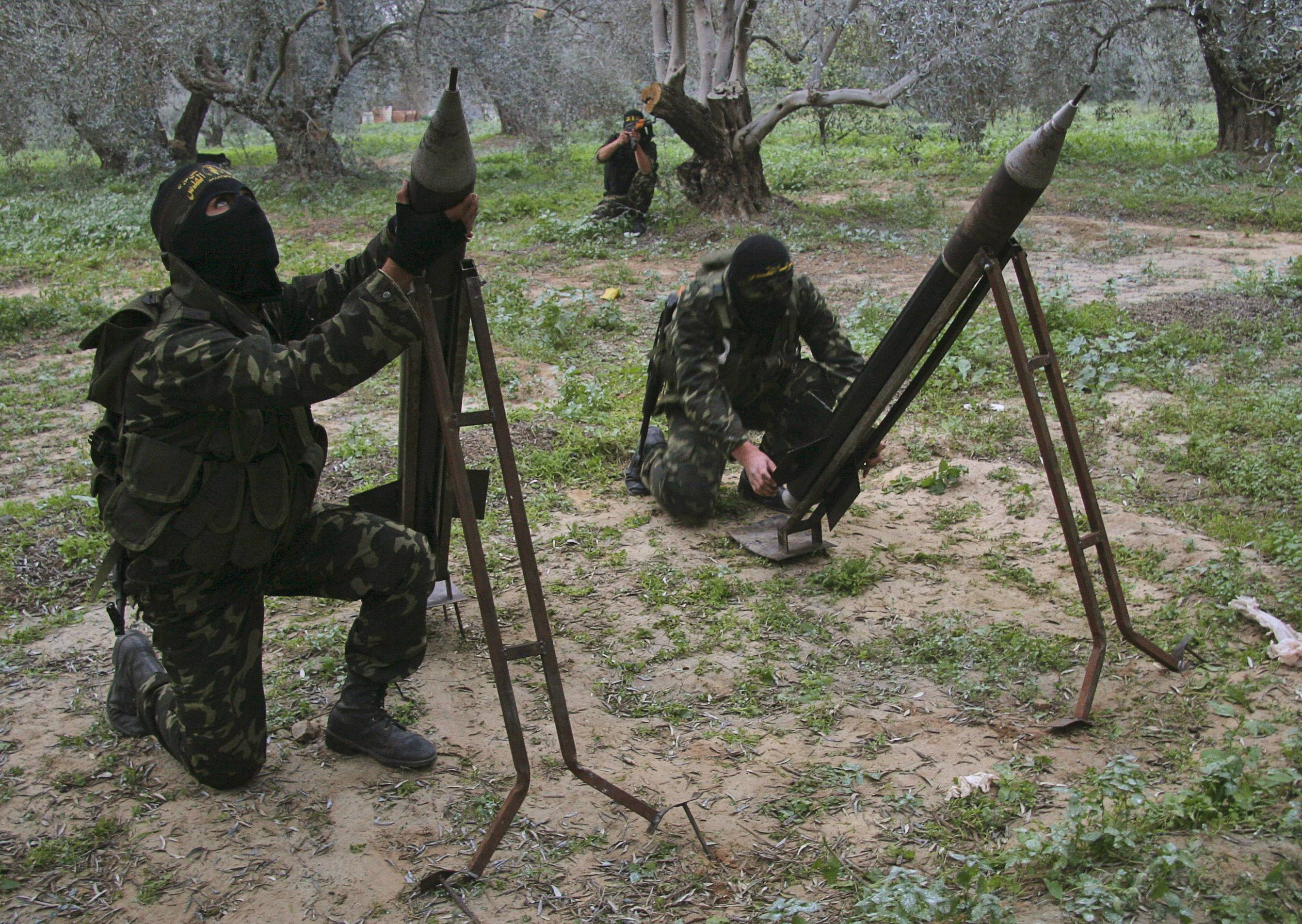 "Masked Palestinian militants from Islamic Jihad in December 2008 place homemade rockets before later firing them into Israel on the outskirts of Gaza City. In 2009, a prominent human rights group said there was ""strong evidence"" that Gaza's Hamas rulers committed war crimes by allowing militants to fire rockets from the territory, killing civilians in Israel."