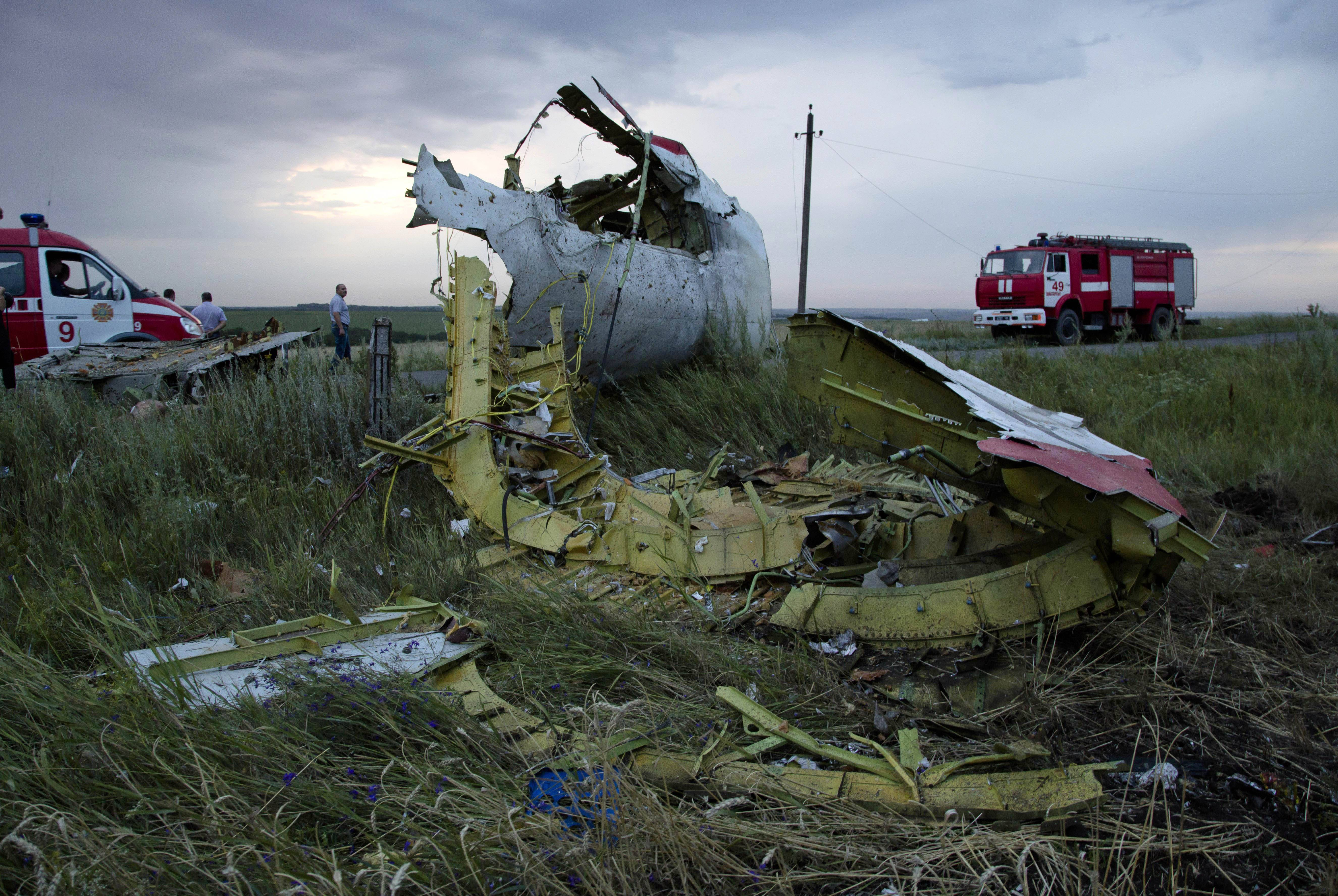 Firefighters arrive at the crash site July 17 of a passenger plane near the village of H