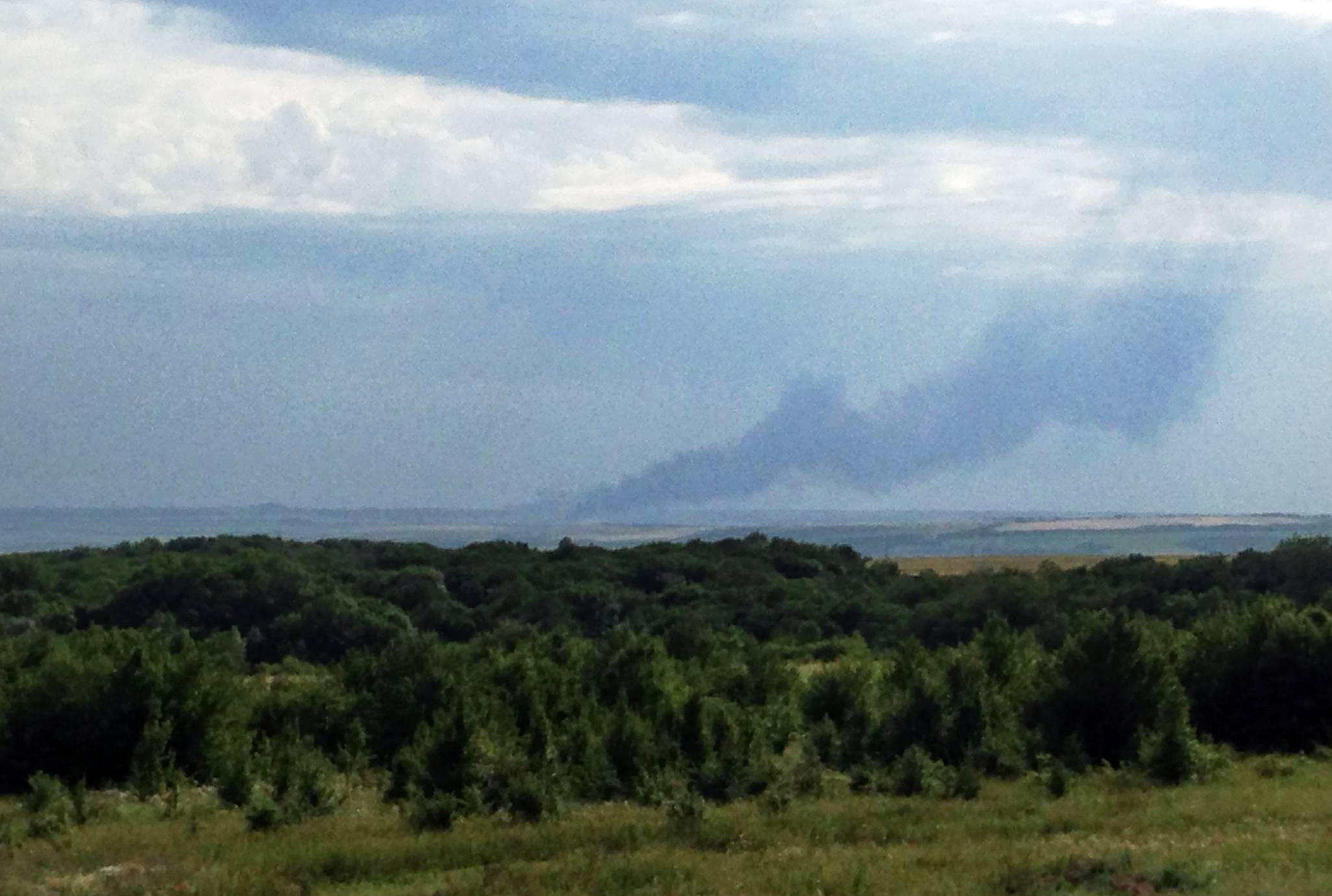 In this July 17 mobile phone photo provided by Andrei Kashtanov, smoke rises from the site where a Malaysia Airlines commercial plane went down in eastern Ukraine.