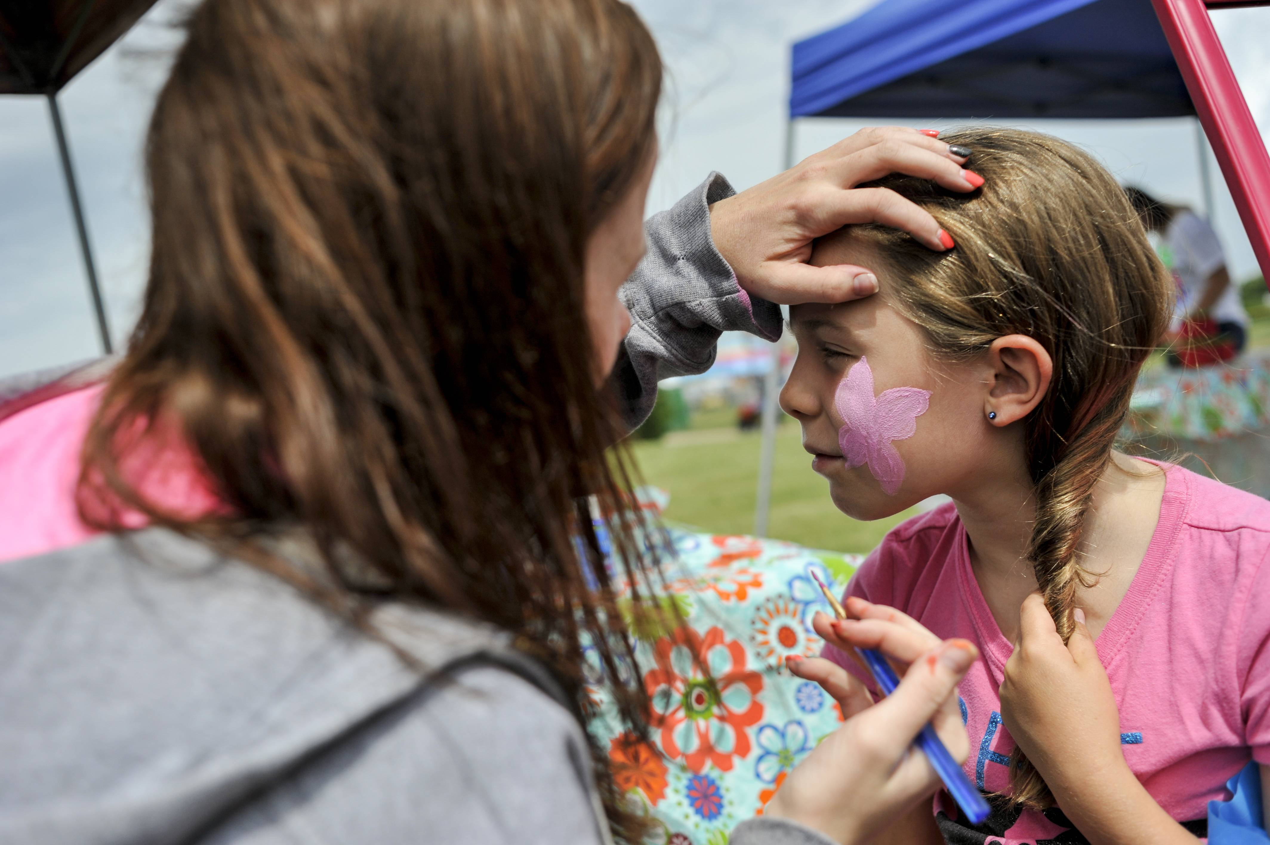Aly Sells of Cary paints a flower on Courtney Cerniglia, 9, of Algonquin at the Founders' Days festival in Algonquin Lakes Park.