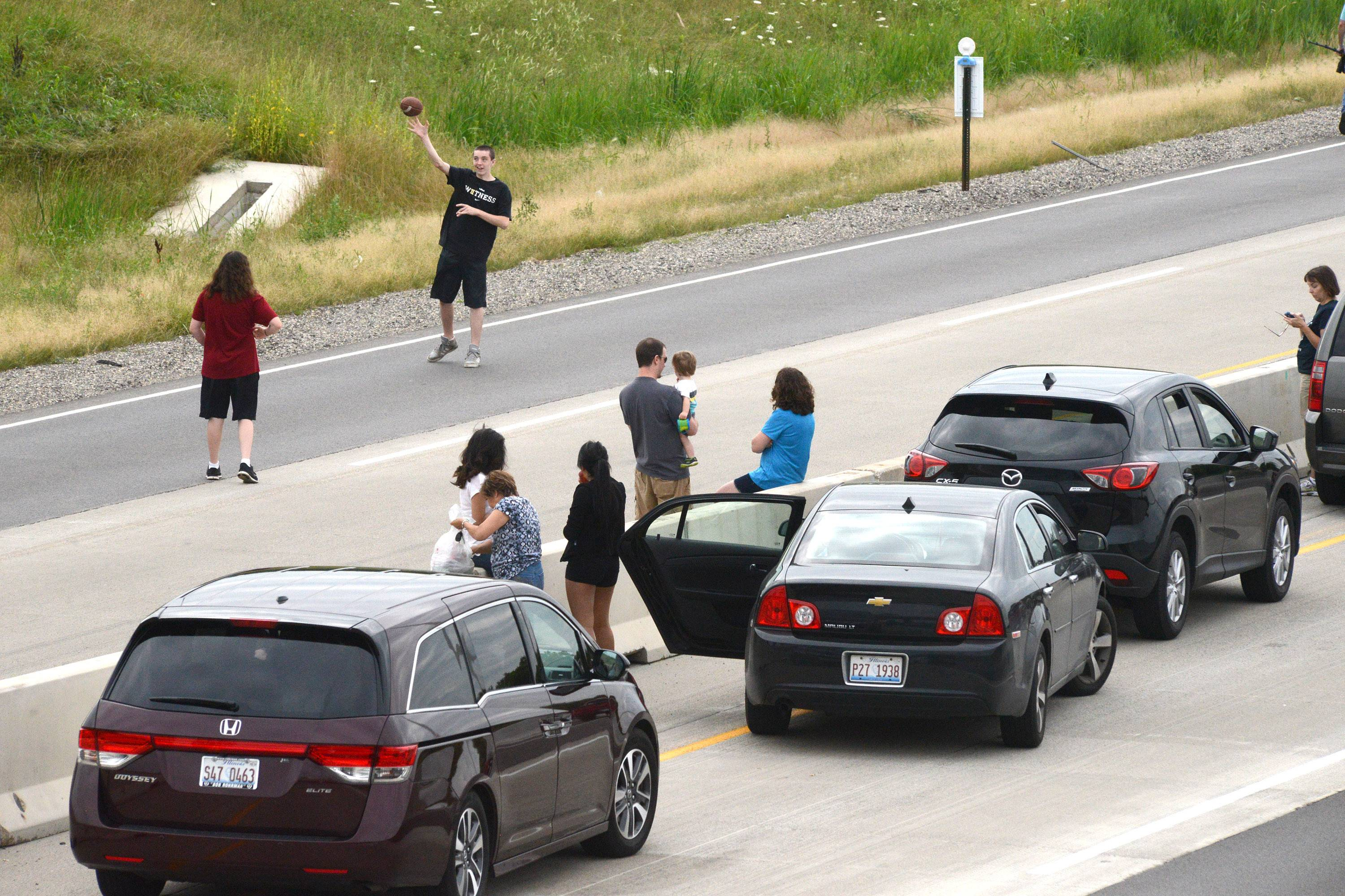 People play football in the blocked eastbound lanes of I-90 after a semitrailer truck engulfed in flames caused a major traffic backup.