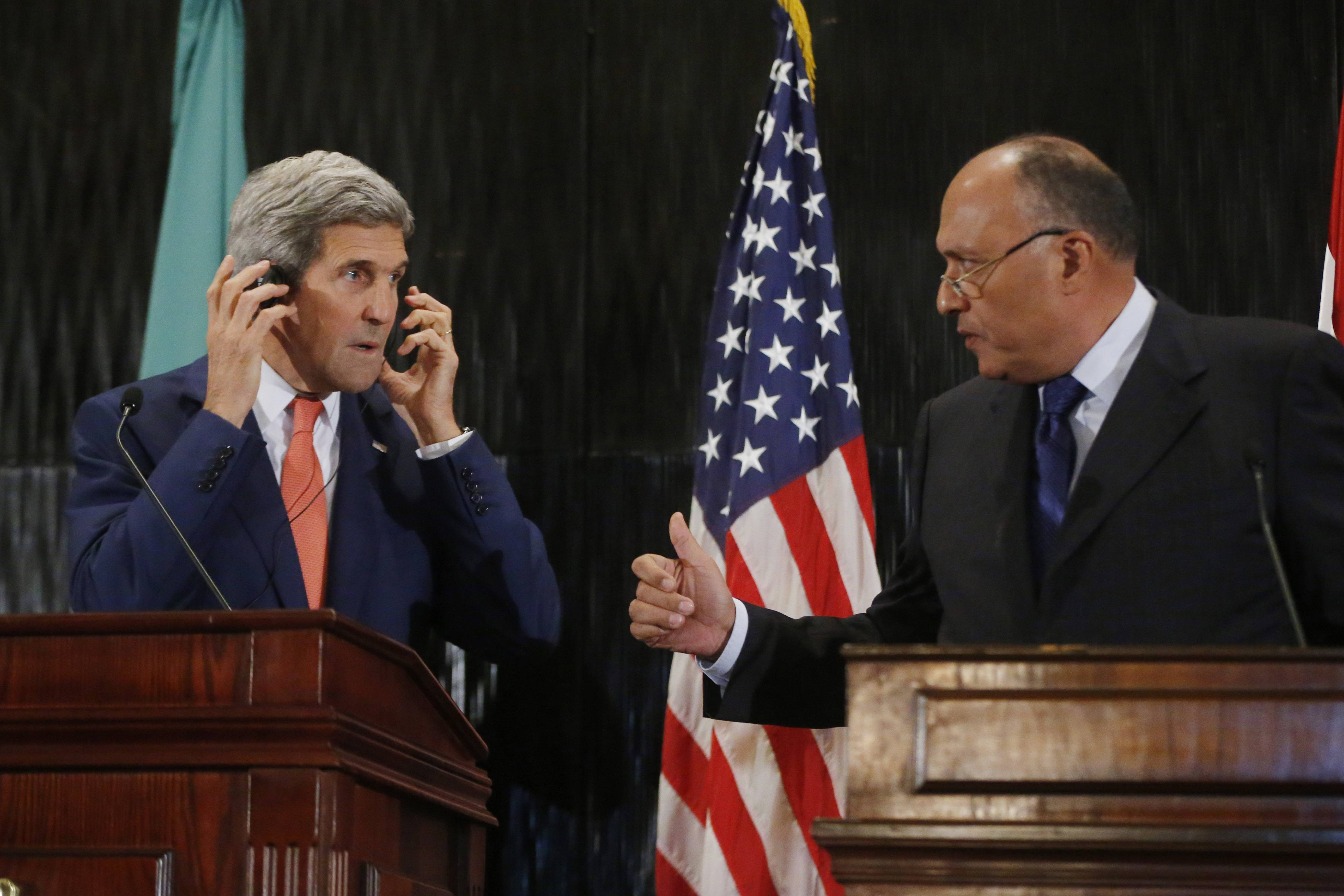 U.S. Secretary of State John Kerry stands with Egypt's Foreign Minister Sameh Shukri during a news conference at a hotel in Cairo, Egypt, Friday. Kerry said he has not yet reached a deal between Israel and Hamas to call a 7-day humanitarian truce in the Gaza war but is continuing work.