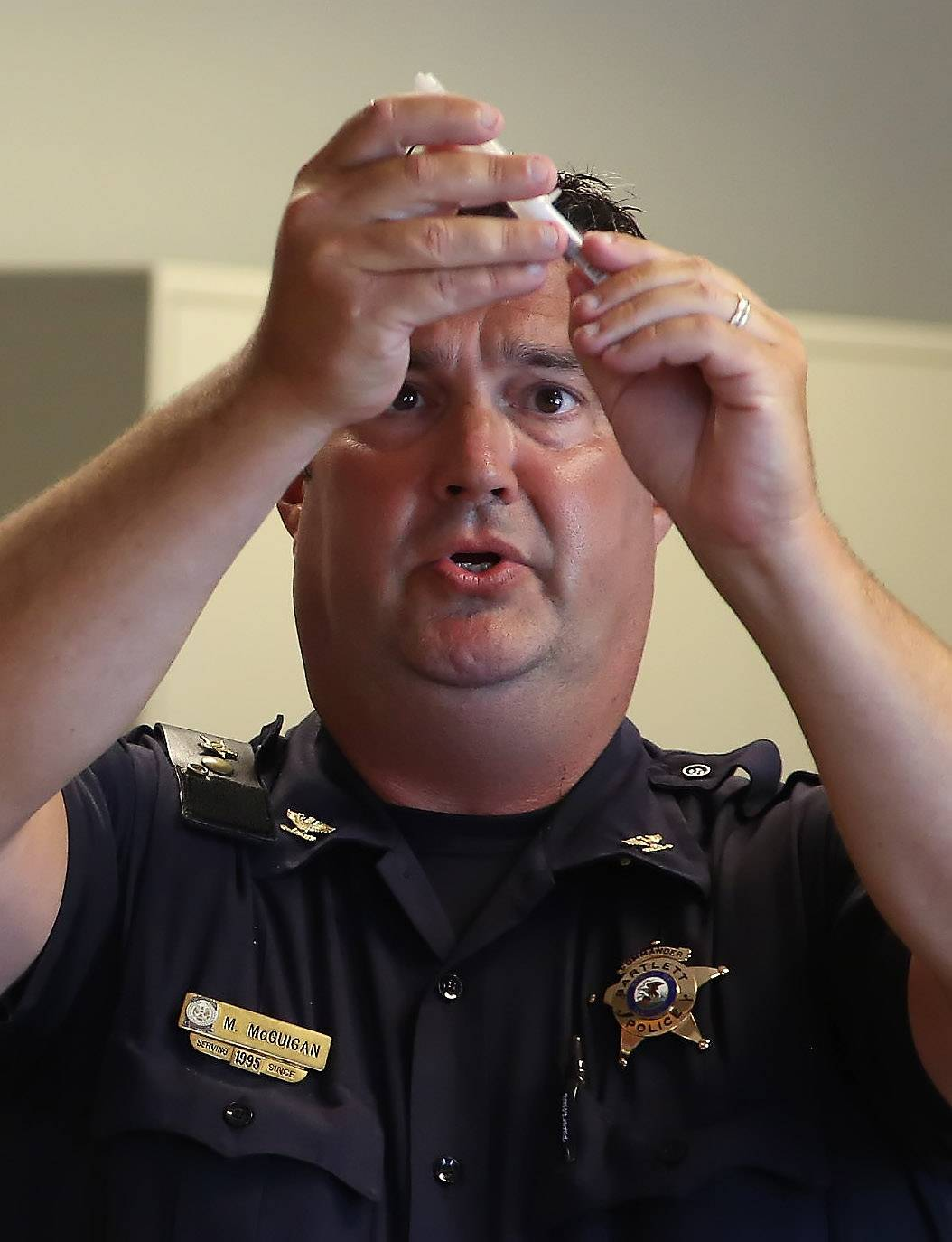 Bartlett police Cmdr. Michael McGuigan demonstrates the naloxone inhaler while training Lake County police officers in the use of the drug, which counteracts the effects of a heroin overdose. Lake County authorities hope to equip every police officer in the county with the spray by Sept. 1.