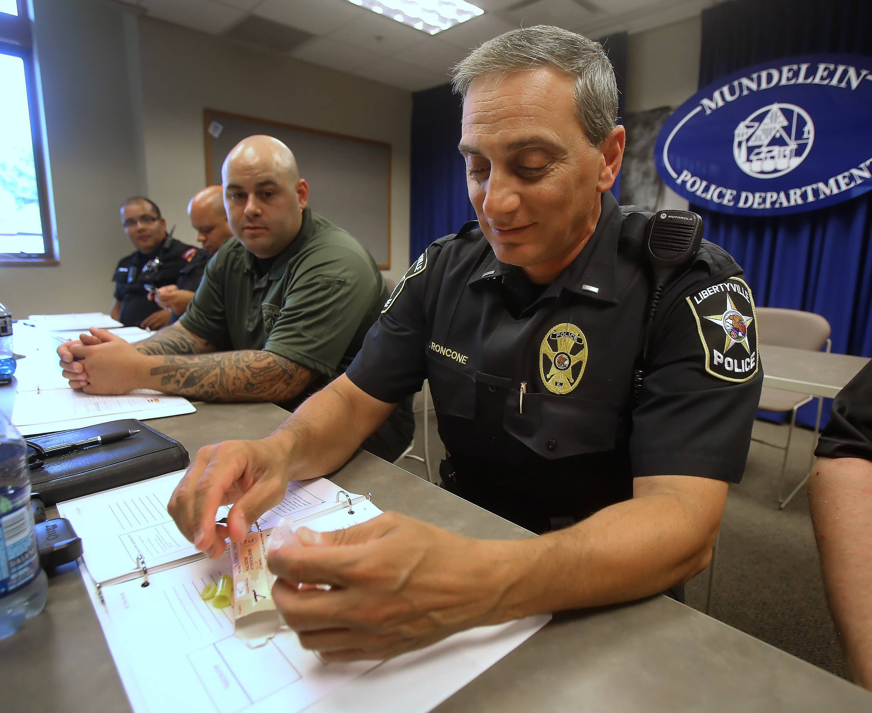 Libertyville police Lt. Ed Roncone practices putting together the naloxone inhaler during a recent training session.