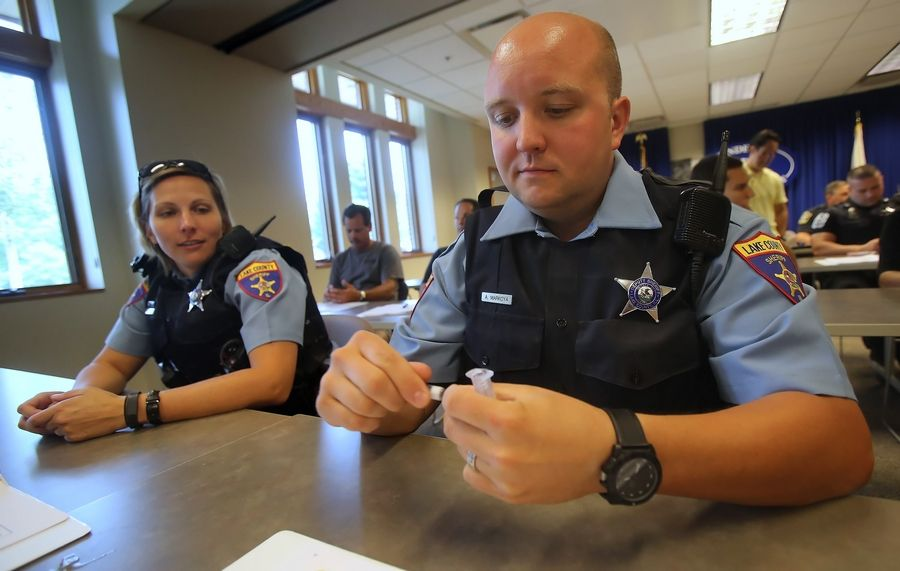 Lake County sheriff's deputies Andy Markoya, right, and Trish List assemble an inhaler during a recent training session.