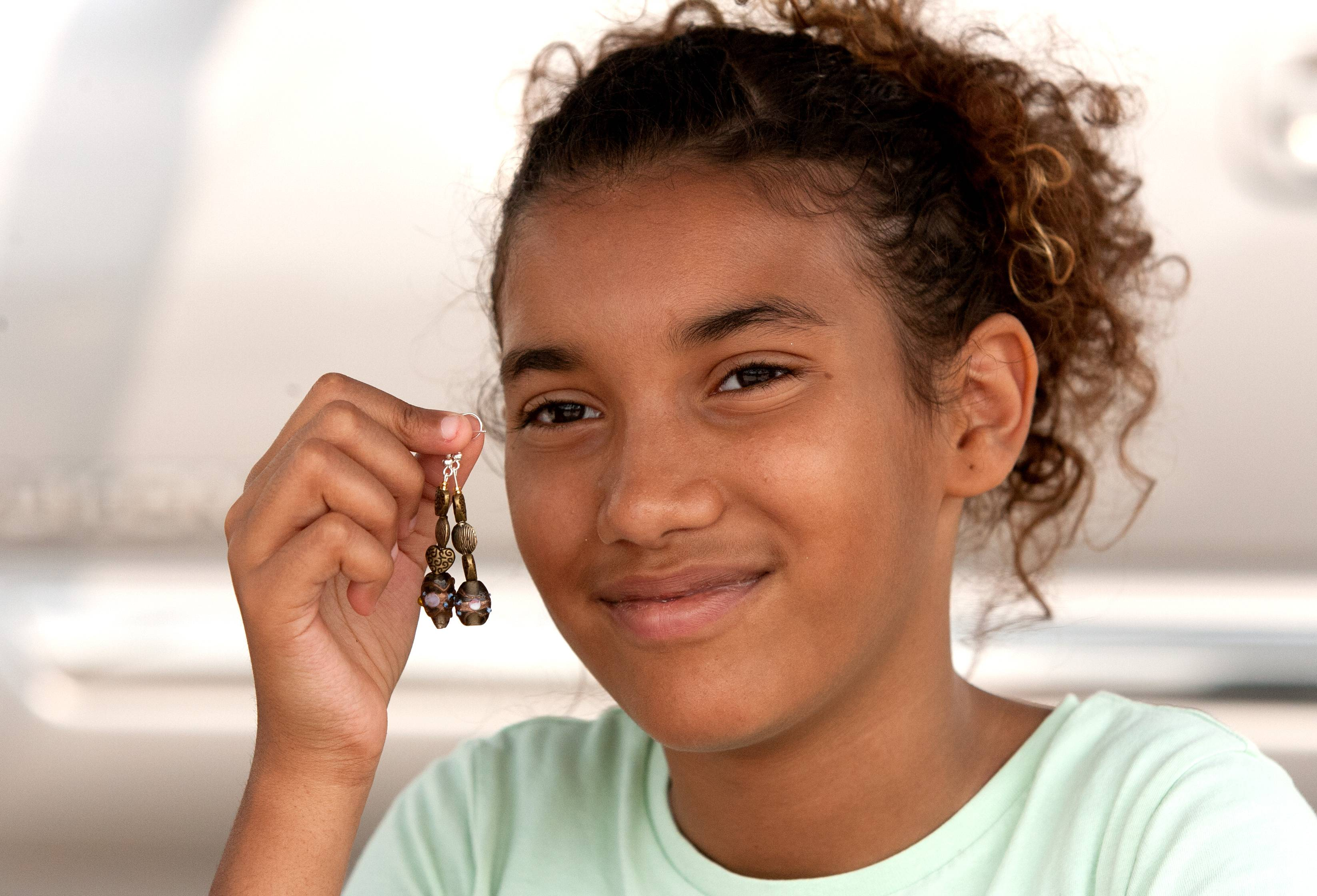 Phynea Mitchell of Designs by Phynea sells handmade earrings as part of the Young Entrepreneurs program at Aurora's farmers markets.