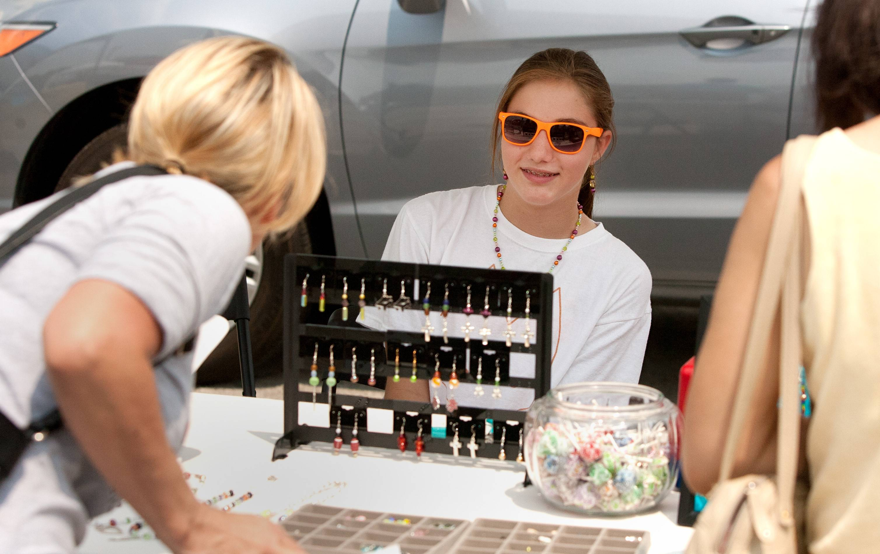 Customers talk with April Kochman about the jewelry she has on display at the Aurora Downtown Farmers Market.