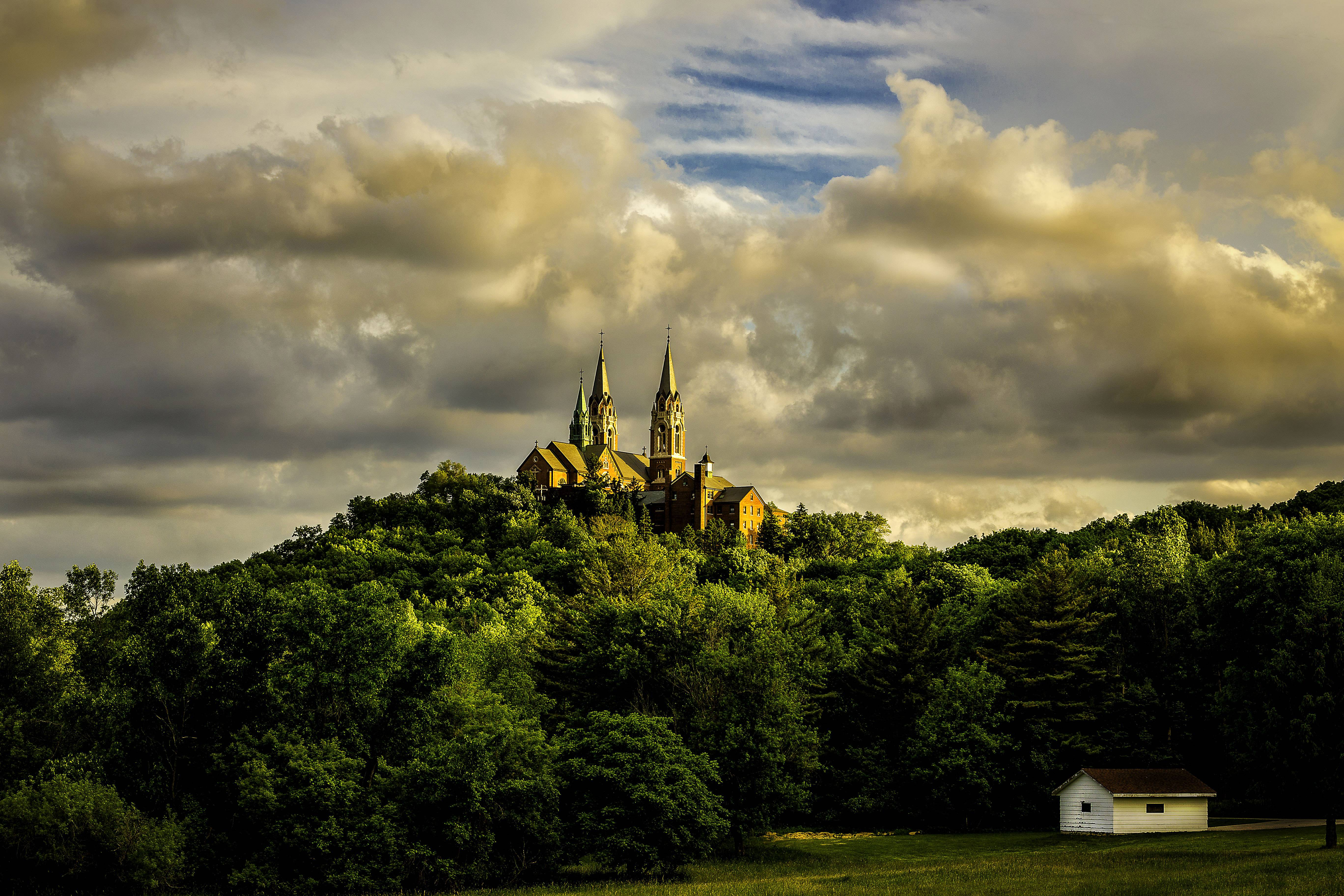 This is Holy Hill Basilica located in Hubertus Wisconsin approximately 30 miles northwest of Milwaukee. The photo was taken approximately 30 minutes before sunset during a mid-June trip I made to photograph the church interior and surrounding grounds. I shot this from a side road location about 1 mile from the structure and my original plan was to get this shot with sunrise light. I got up at 4 a.m., was on site by 4:45 a.m., but the entire grounds were completely covered with fog. I went back that evening and was blessed with beautiful sunset light.