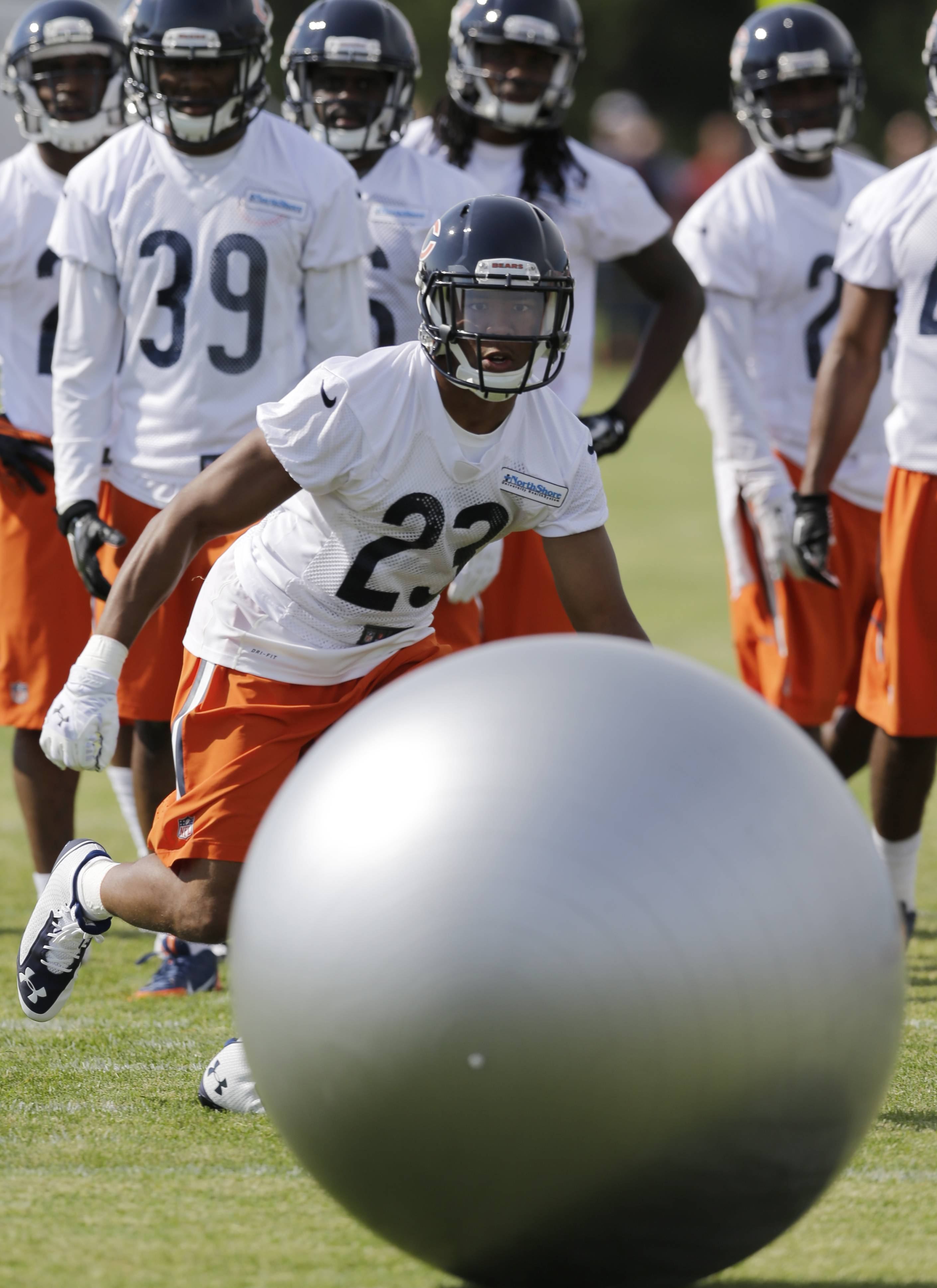 Bears cornerback Kyle Fuller (23) works with a ball as teammates look on at Olivet Nazarene University on Friday. Fuller, the Bears' first-round selection in May, picked off the first pass of 11-on-11 drills and added another pick later in practice.