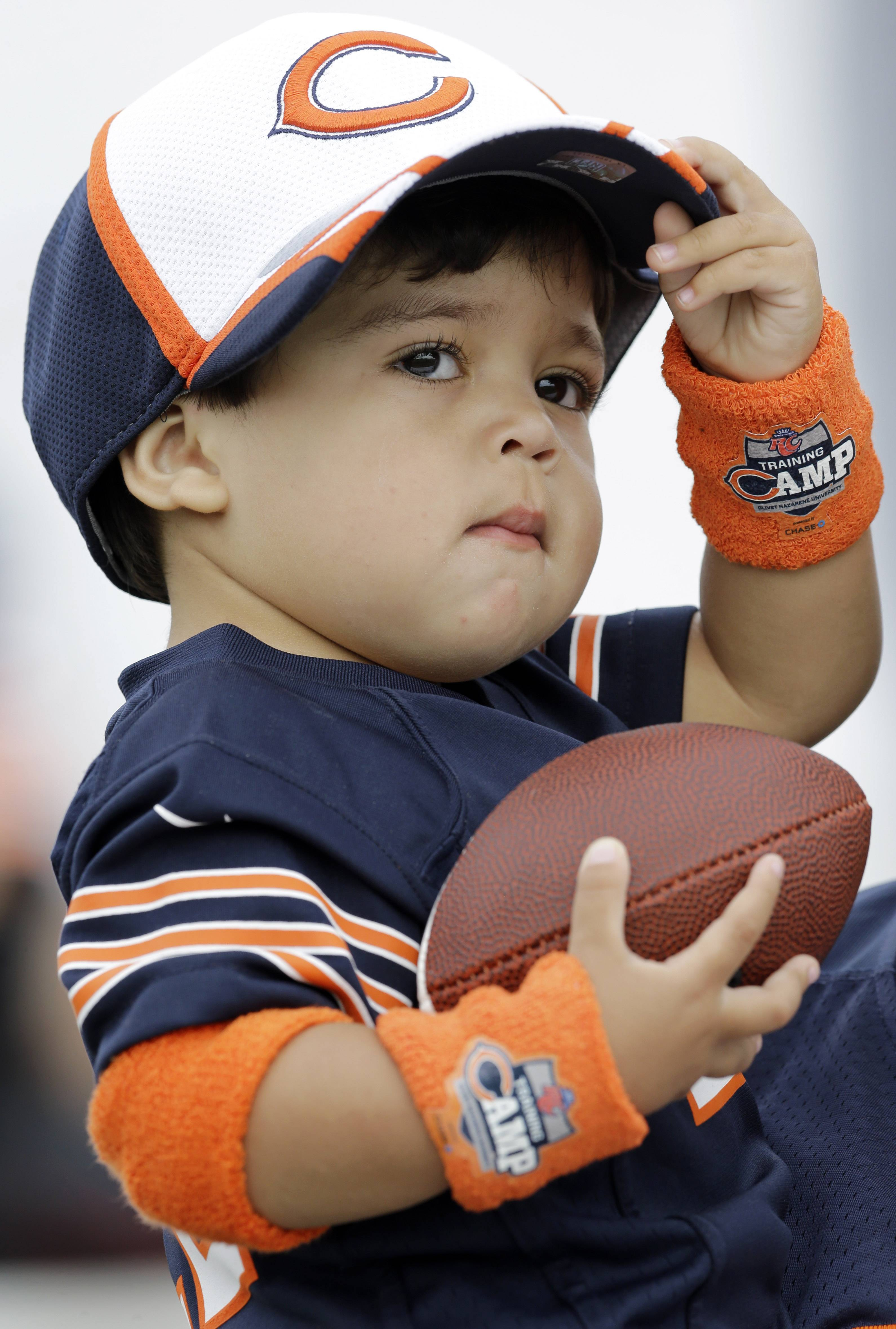 Jiraiya Dica, 2,  watches Chicago Bears players during the team's NFL football training camp at Olivet Nazarene University on Friday, July 25, 2014, in Bourbonnais, Ill.
