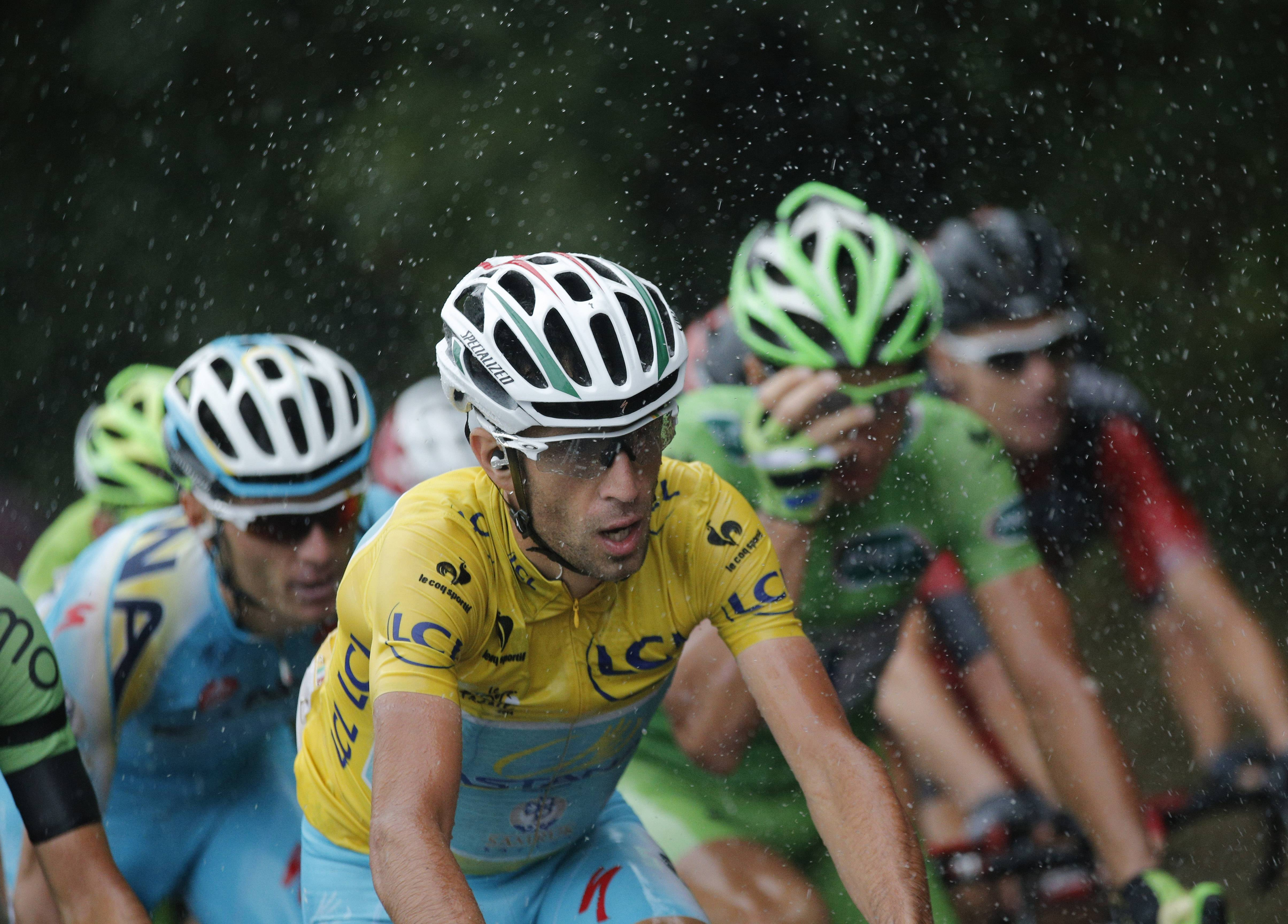 Italy's Vincenzo Nibali, wearing the overall leader's yellow jersey, rides in the rain during the nineteenth stage of the Tour de France cycling race over 208.5 kilometers (129.6 miles) with start in Maubourguet and finish in Bergerac, France, Friday, July 25, 2014.