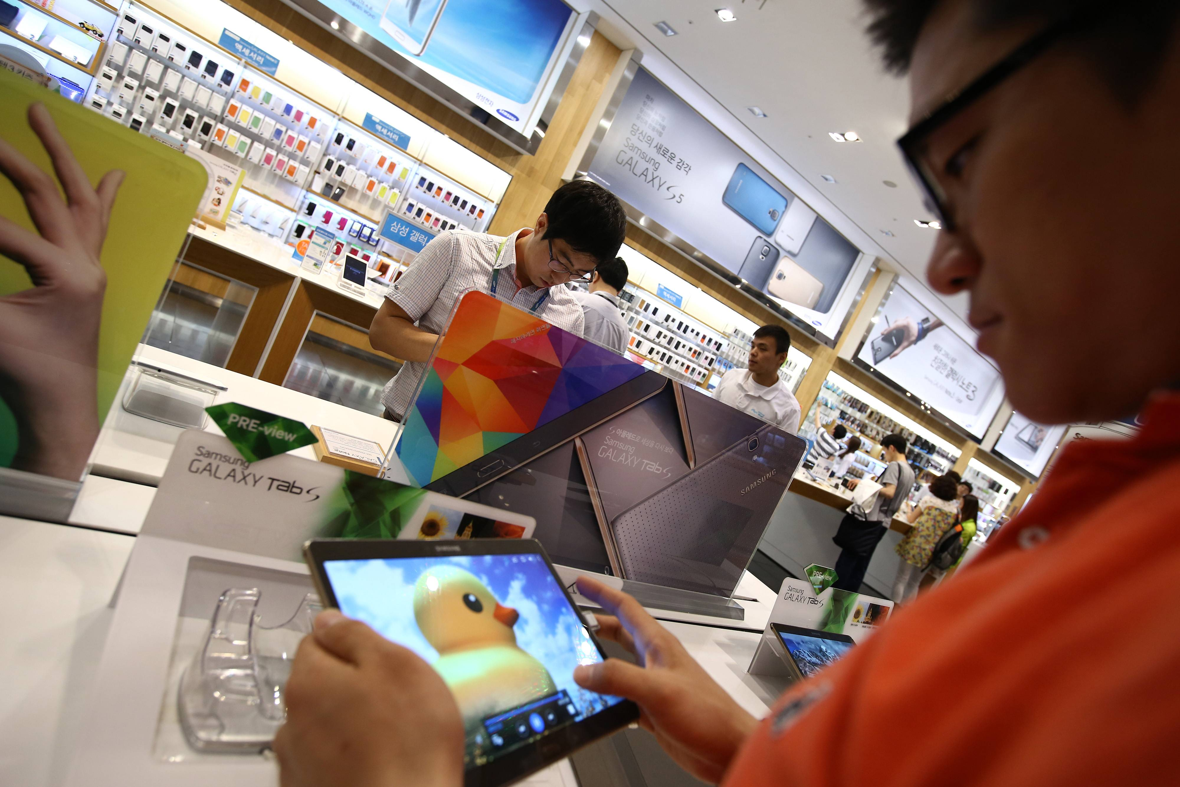 Customers try out Samsung Electronics Co. Galaxy Tab S tablet computers. The Lee family has held sway over Samsung Electronic's 74 companies, but the younger Lee will have to loosen the family's hold and ease protections against outside shareholders just as Samsung Electronics faces rising challenges to its position at the top of the smartphone market.