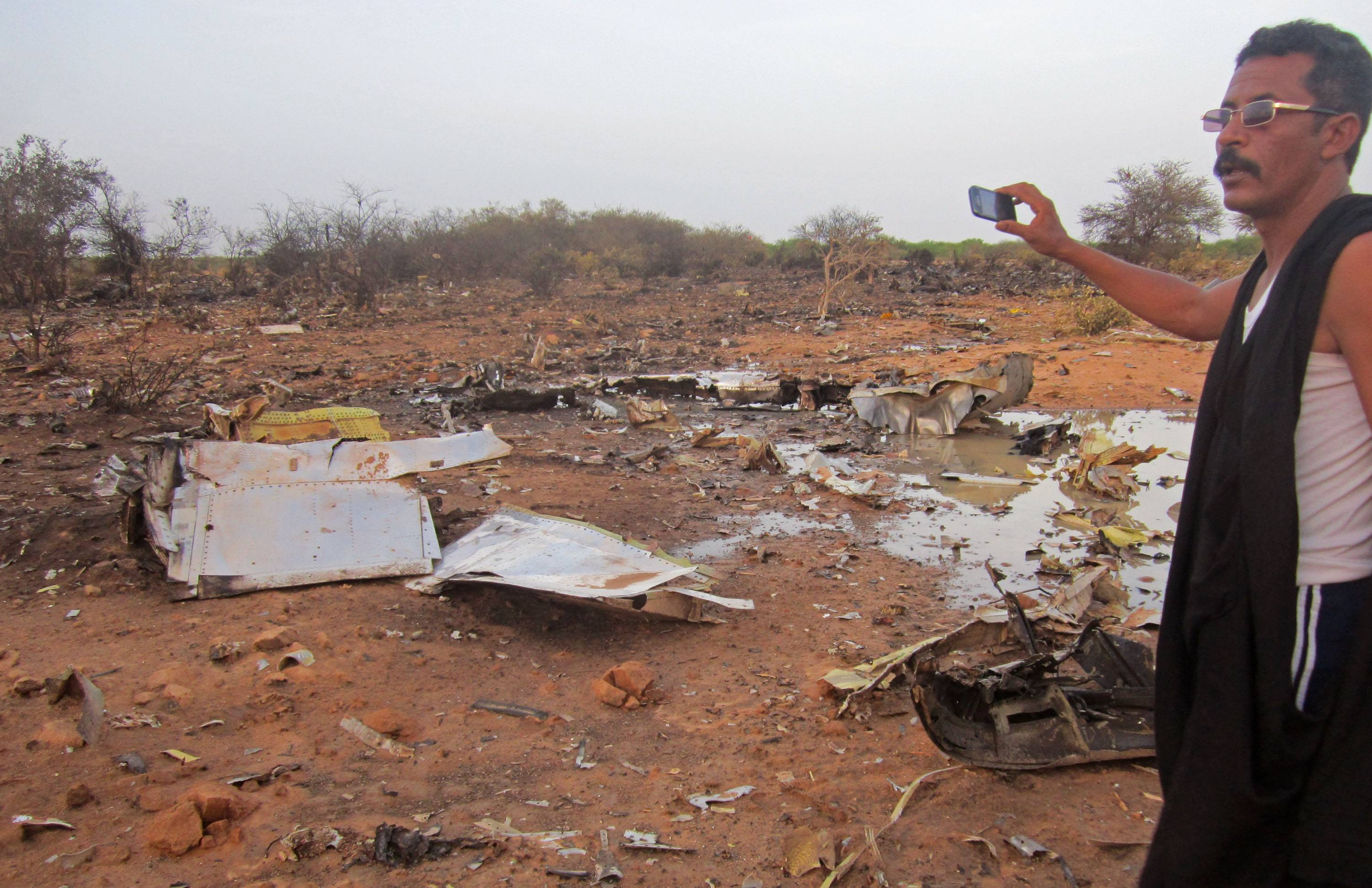 This photo provided on Friday, by the Burkina Faso Military shows a man at the site of the plane crash in Mali. French soldiers secured a black box from the Air Algerie wreckage site in a desolate region of restive northern Mali on Friday, the French president said. Terrorism hasn't been ruled out as a cause, although officials say the most likely reason for the catastrophe that killed all onboard is bad weather. At least 116 people were killed in Thursday's disaster, nearly half of whom were French.