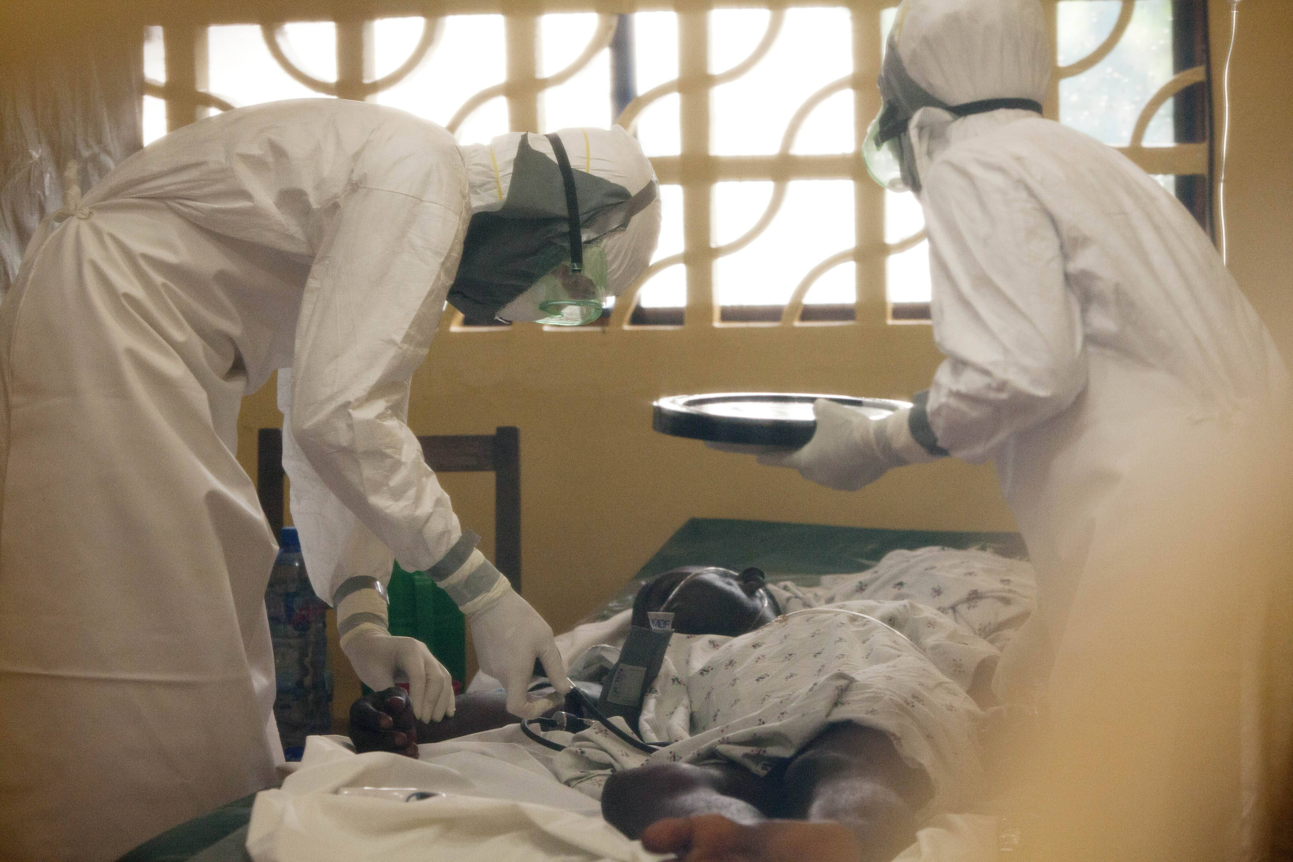 In this 2014 photo provided by the Samaritan's Purse aid organization, Dr. Kent Brantly, left, treats an Ebola patient at the Samaritan's Purse Ebola Case Management Center in Monrovia, Liberia. On Saturday, the North Carolina-based aid organization said Brantly tested positive for the disease and was being treated at a hospital in Monrovia.