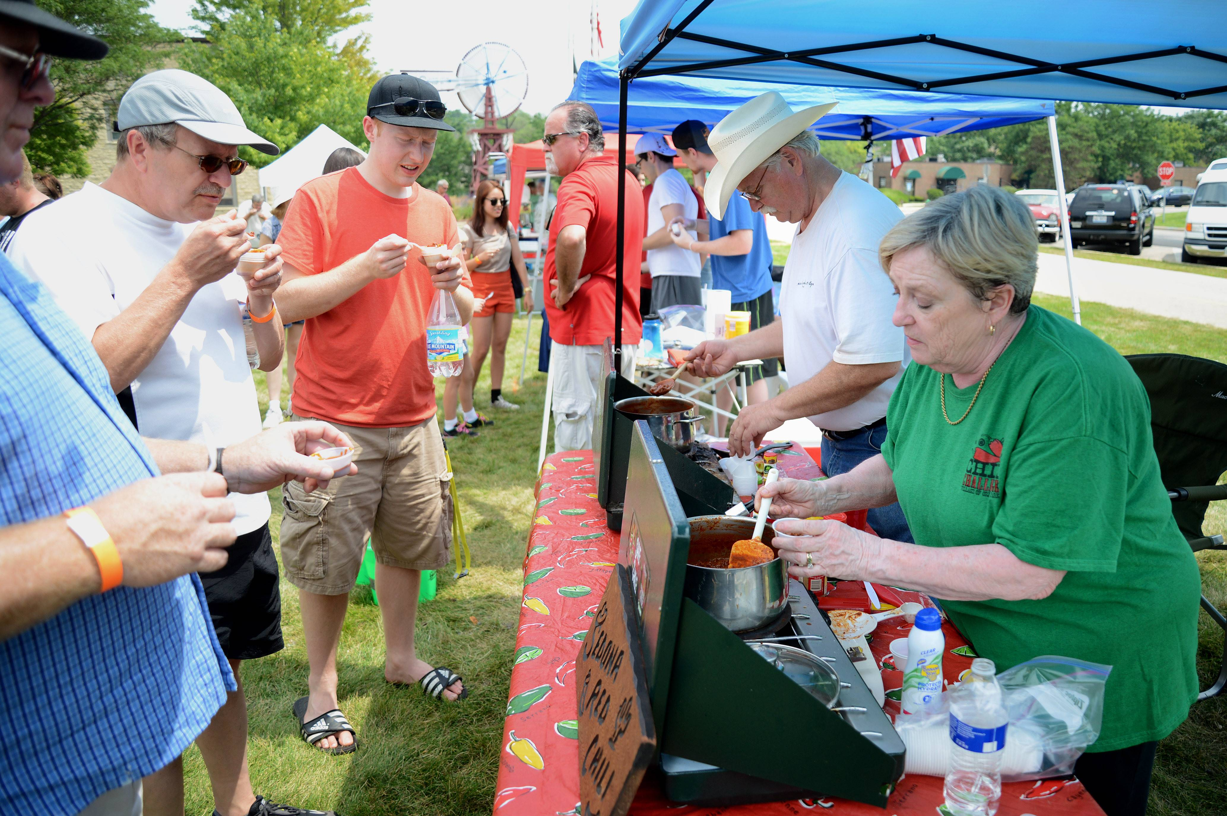 Gloria Stevens of Homer Glen scoops out samples of her Sedona Red Chili to hungry patrons at the State Championship Chili Cook-Off Saturday in Batavia. Her husband, Mike, right, has competed since the beginning, while Gloria started a few years later.