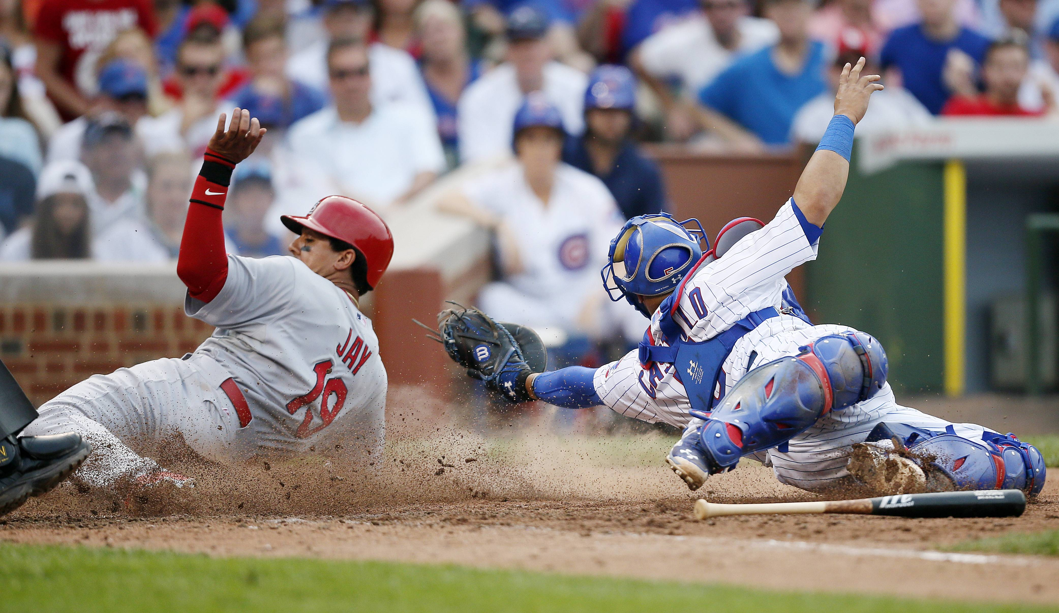 The St. Louis Cardinals' Jon Jay, left, scores past Cubs catcher Welington Castillo during Saturday's game at Wrigley Field. The Cubs lost 6-3.