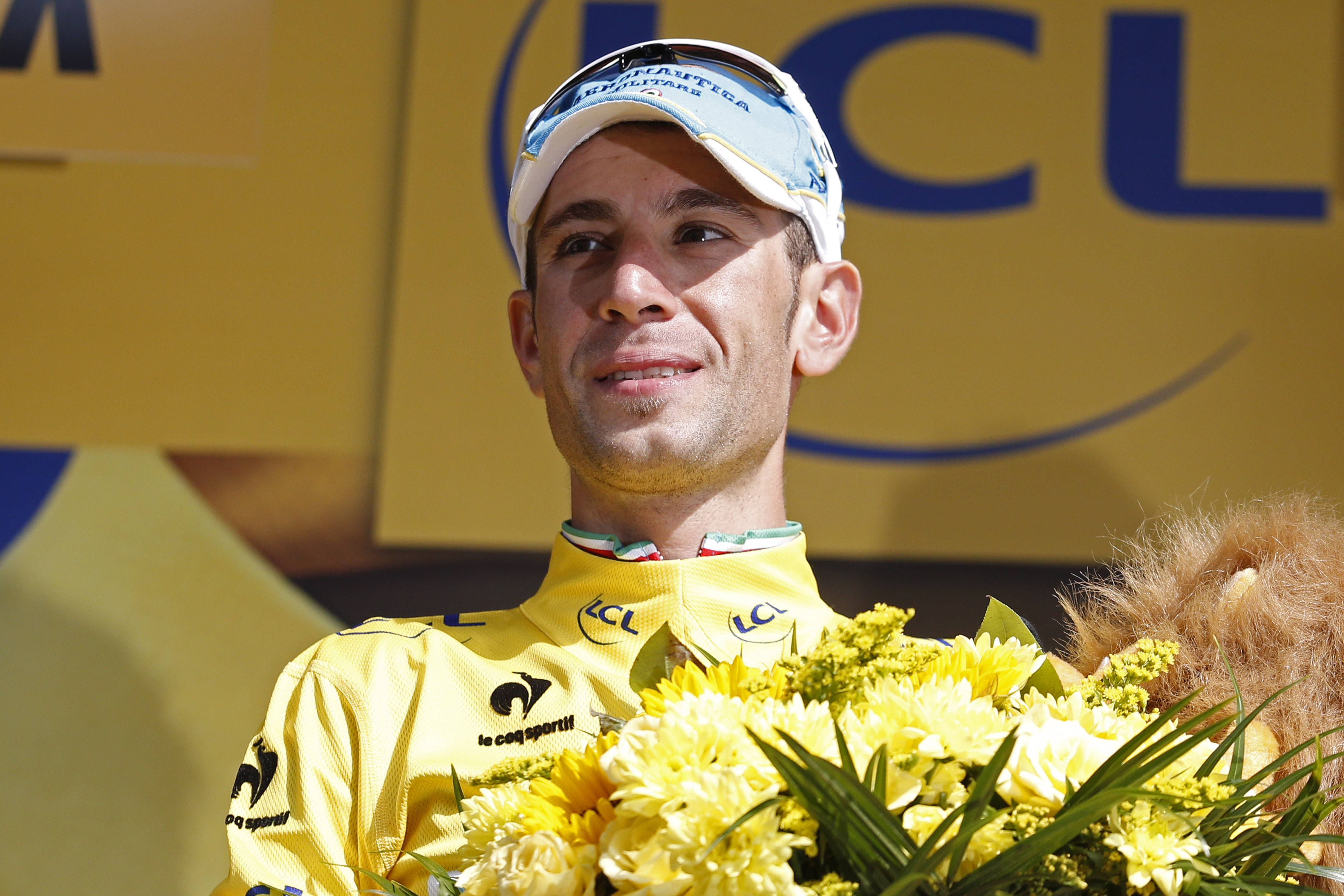 Italy's Vincenzo Nibali, wearing the overall leader's yellow jersey, celebrates on the podium of the twentieth stage of the Tour de France cycling race, an individual time-trial over 54 kilometers (33.6 miles) with start in Bergerac and finish in Perigueux, France, Saturday, July 26, 2014.