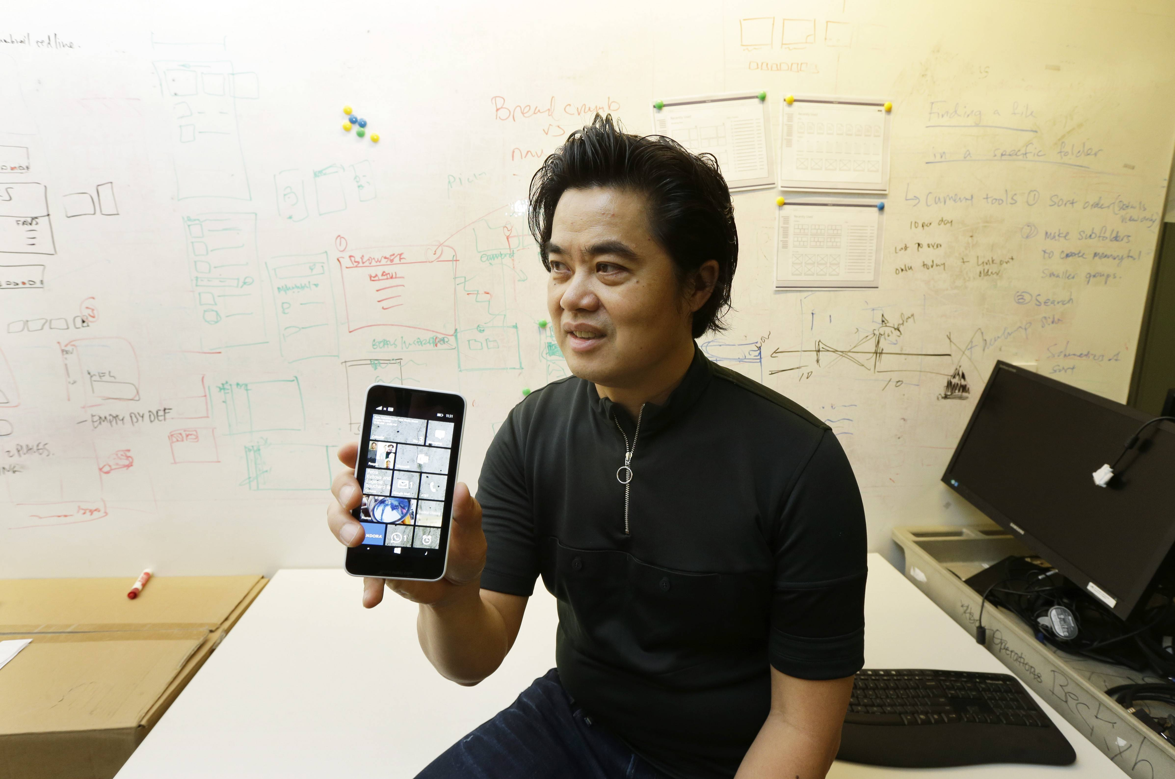 "Albert Shum, who heads interaction design across a range of Microsoft products including personal computer operating systems, Xbox game consoles, and phones, poses with a Windows phone in front of a whiteboard used to brainstorm ideas, at the Windows Design Studio in Redmond, Wash. A former designer for shoemaker Nike, Shum was part of the team that revolutionized the Windows Phone design to feature the boxy, so-called ""live tiles"" that are central to the touch-based interface in Windows 8."