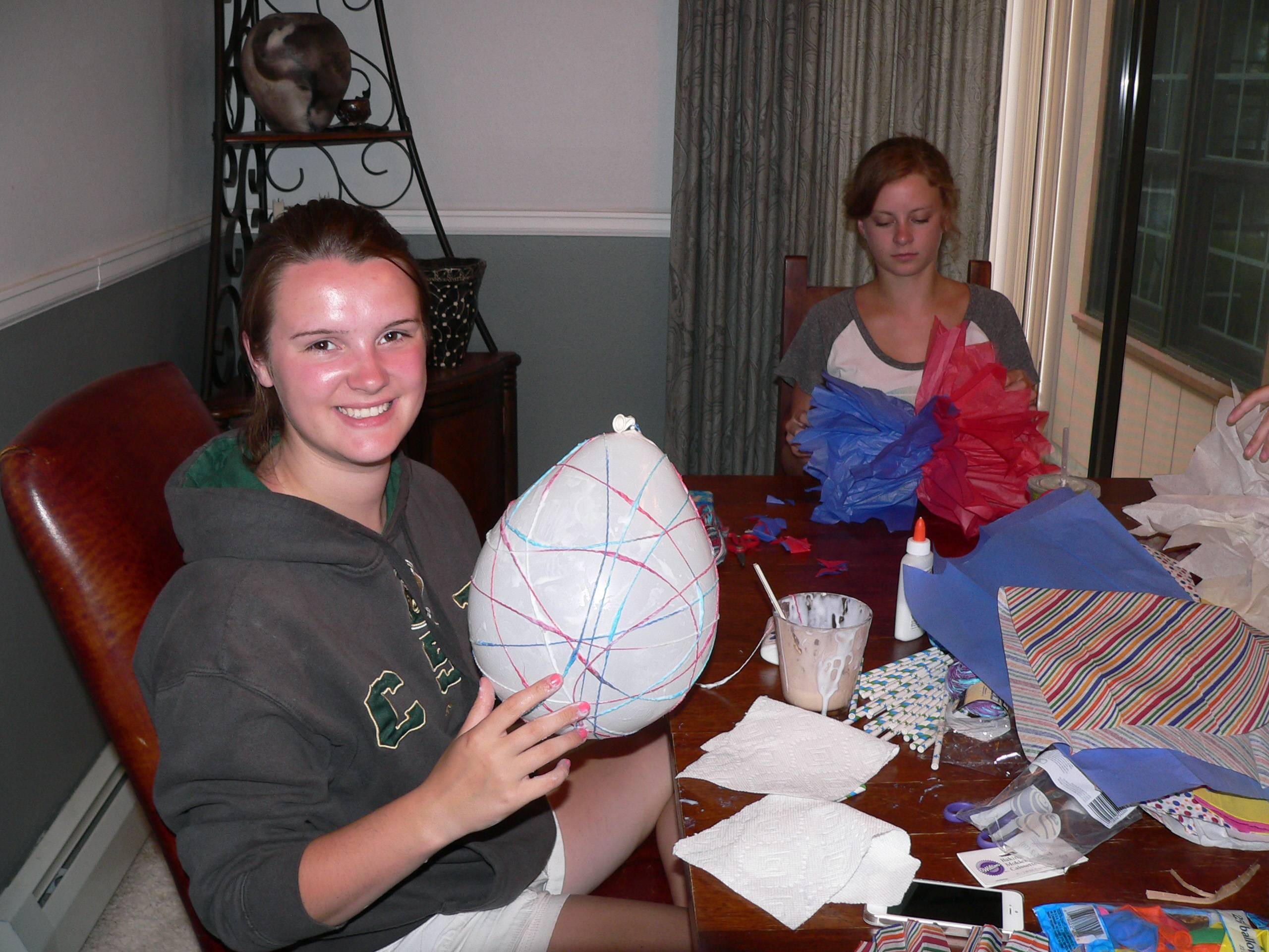 Hope Clarke, 16, left, wraps yarn soaked in craft glue around a balloon while Hadley Hagemann, 16, works on a giant tissue pom-pom at a crafting night hosted at Clarke's house in Arvada, Colo. After the glue dried, Clarke popped and removed the balloon to reveal a colorful orb for hanging.
