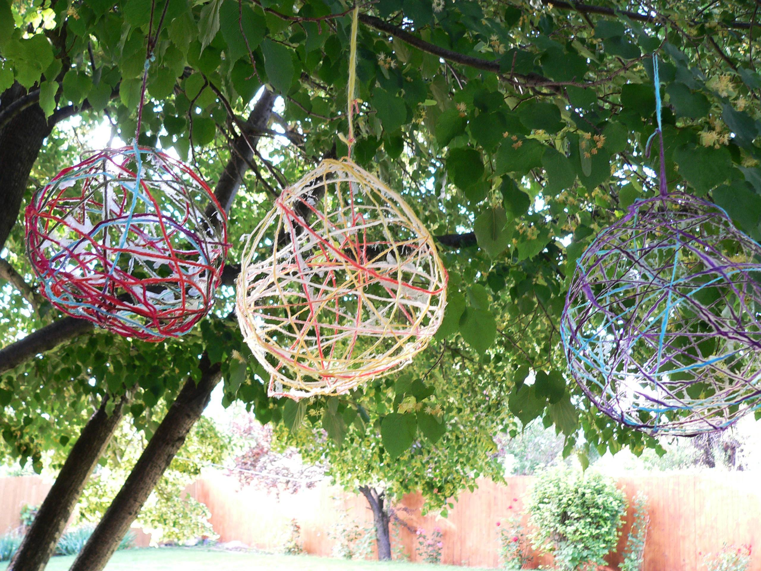 Colorful orbs -- made from glue-soaked yarn wrapped around balloons -- hang in a tree in Arvada, Colo. This and other crafts were featured at a teen crafting party.