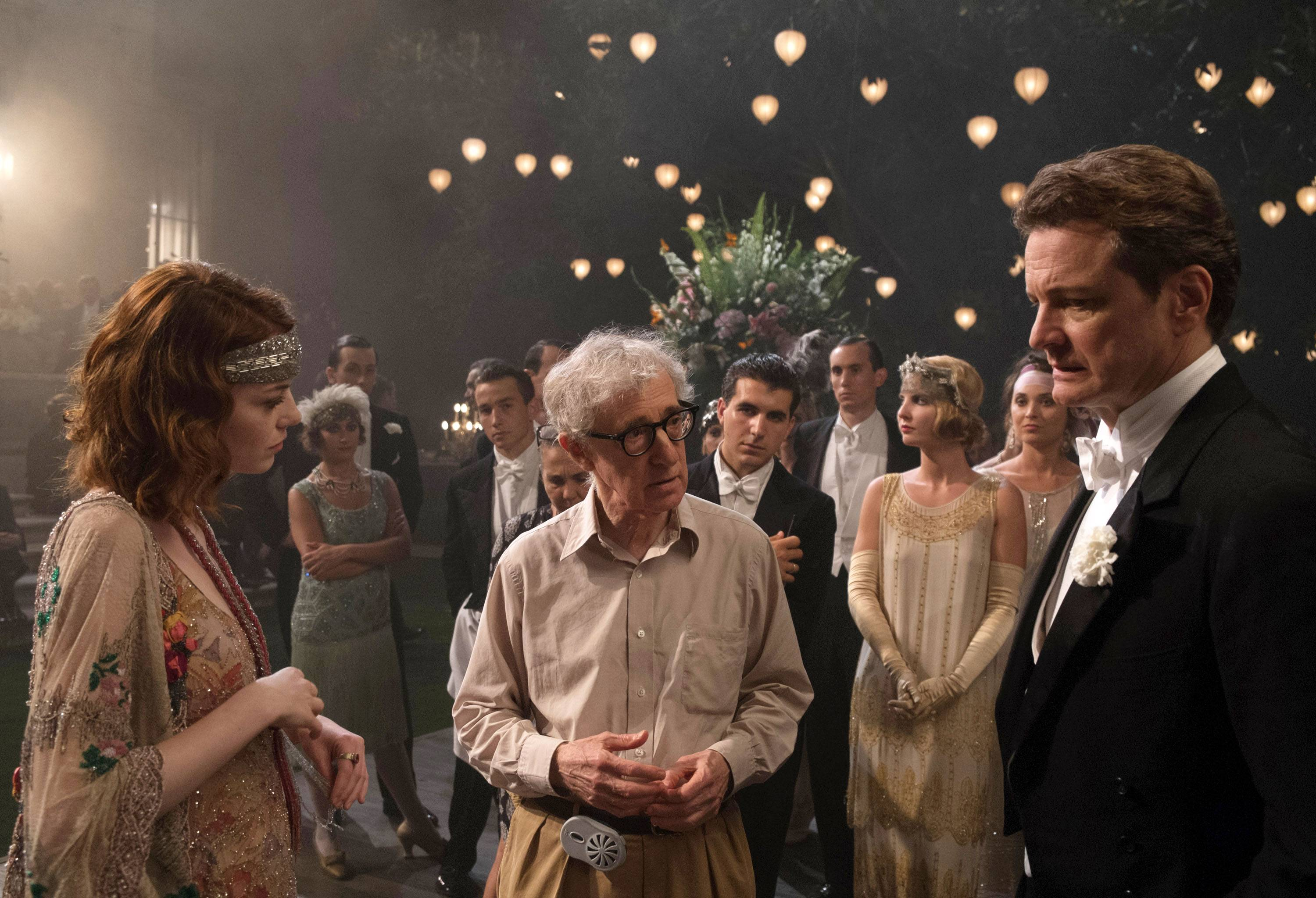 "Director Woody Allen, center, discusses a scene with actors Emma Stone, left, and Colin Firth on the set of ""Magic in the Moonlight."""