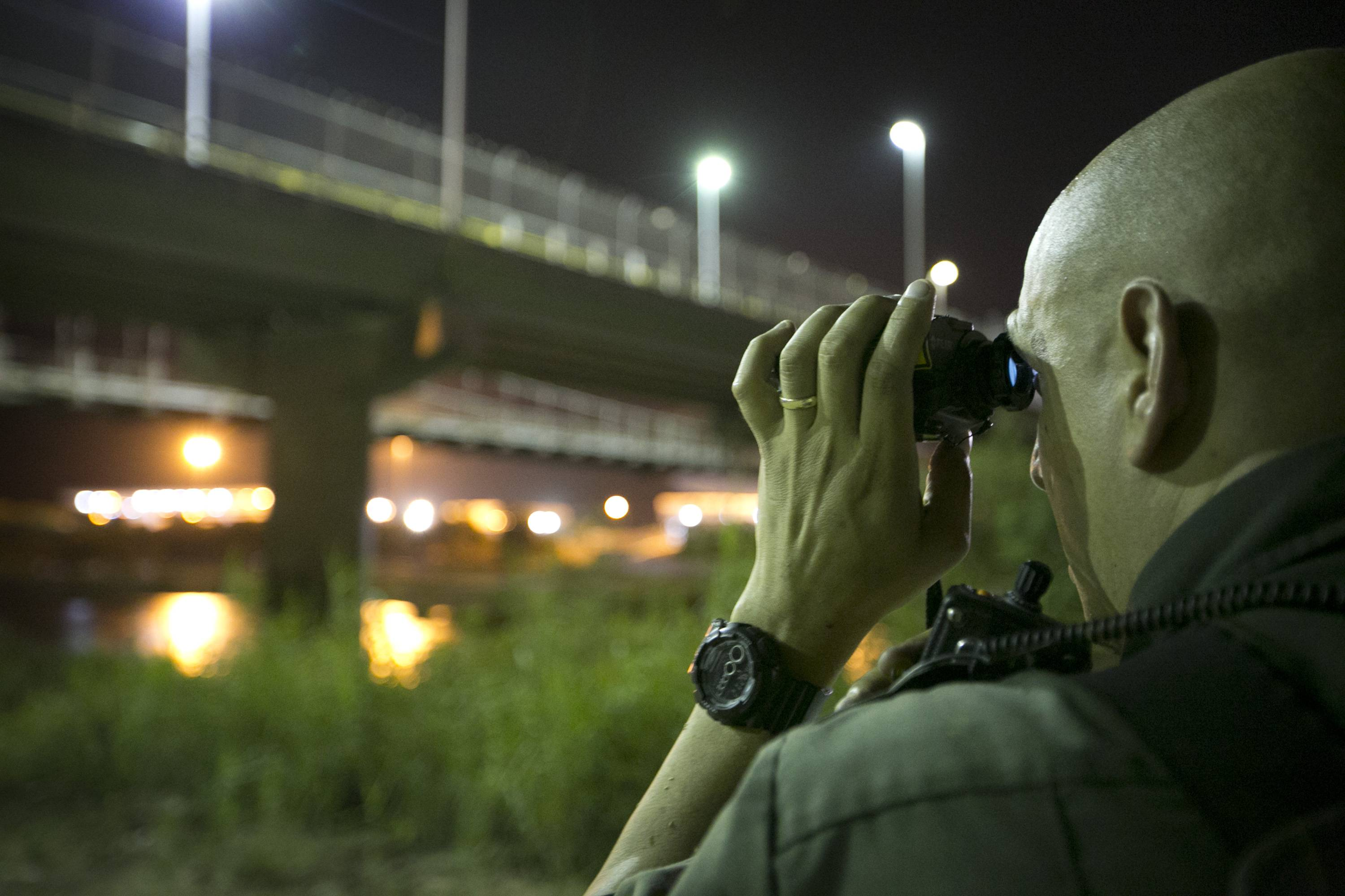 In this Wednesday photo, a U.S. Border Patrol agent keeps watch in Roma, Texas, across the Rio Grande from Ciudad Miguel Aleman, Tamaulipas, Mexico.