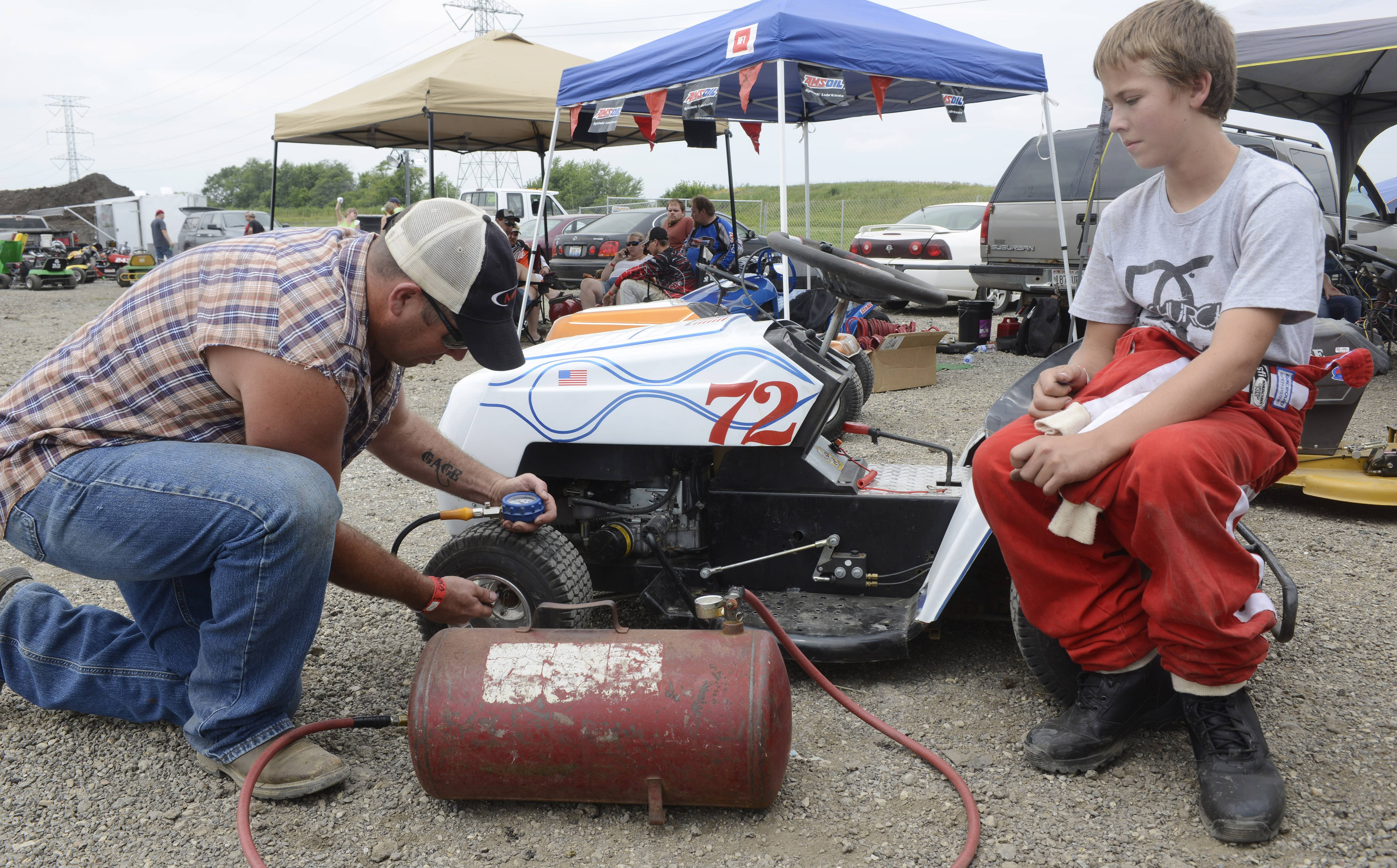 "Brian Bennett of Coffeyville, Kansas, fills the tires on his mower while his son, Gage, watches before the ""Mow Down Showdown"" races Saturday at Lake County Fair in Grayslake."