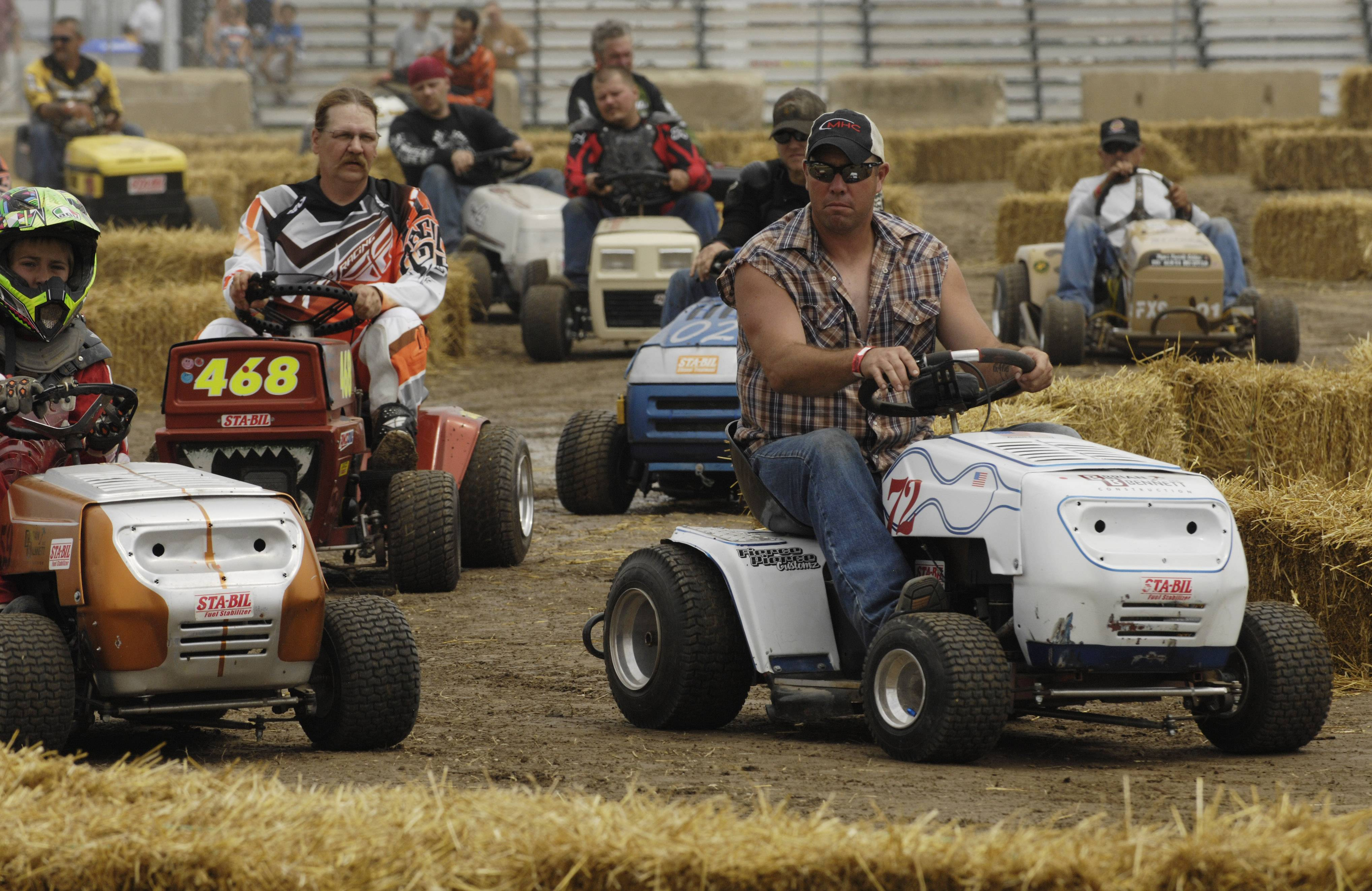 "Competitors in the ""Mow Down Showdown"" races, including Brian Bennet of Coffeyville, Kansas, right, participate in a pre-race parade Saturday at the Lake County Fair in Grayslake."