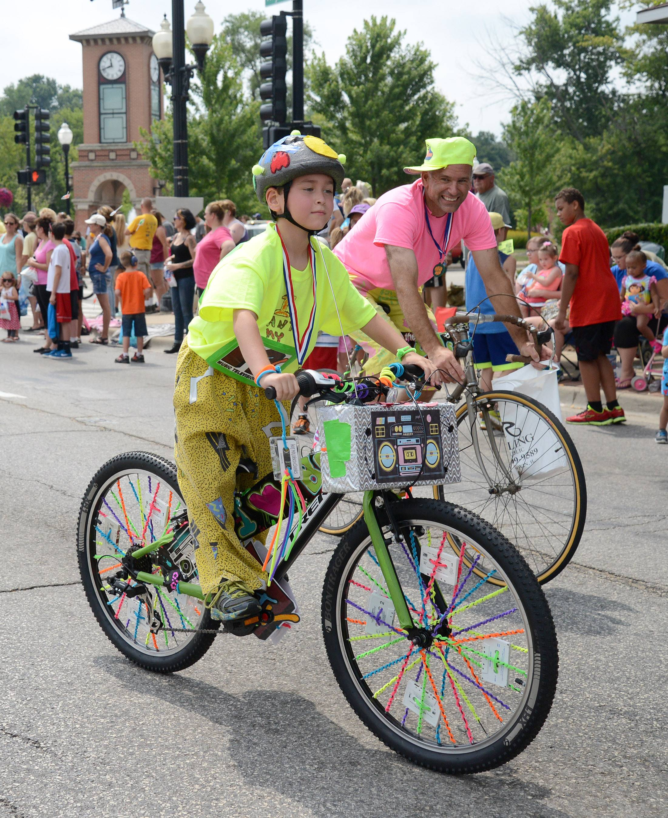 Ethan Fiedler, 7, of Algonquin displays his winning entry in the Founders' Days Bike Decorating Contest during the festival's parade in Algonquin on Saturday. Ethan, who just purchased this new bike, rides with his father, Ray, right.