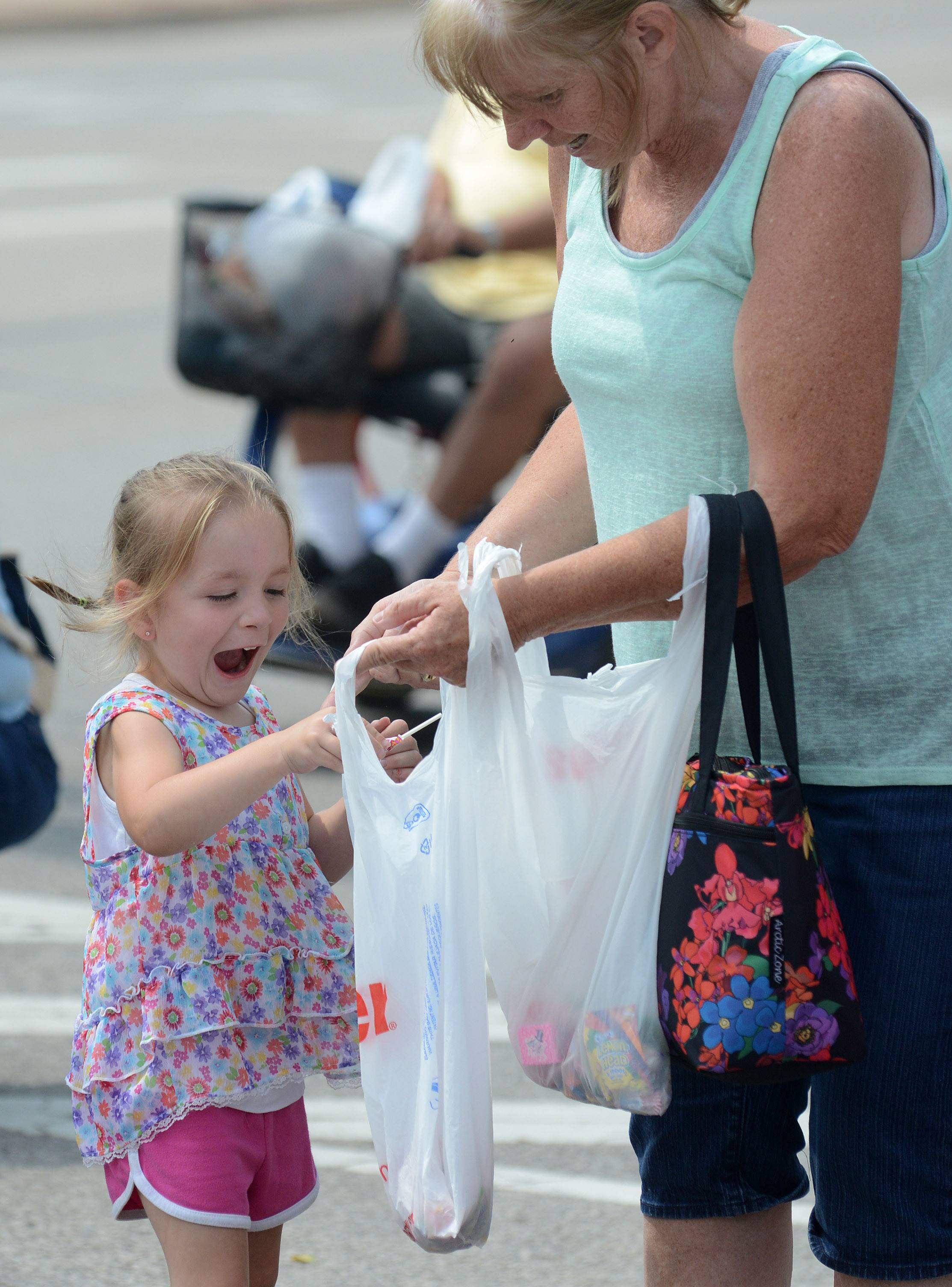 Karli Helmer, 4, of Janesville, Wisconsin, fills her bag with candy with help from her grandmother, Judy Atkinson of Belvidere, at the Founders' Days parade in Algonquin on Saturday. Atkinson, a former Carpentersville resident, brought her grandchildren to the parade.
