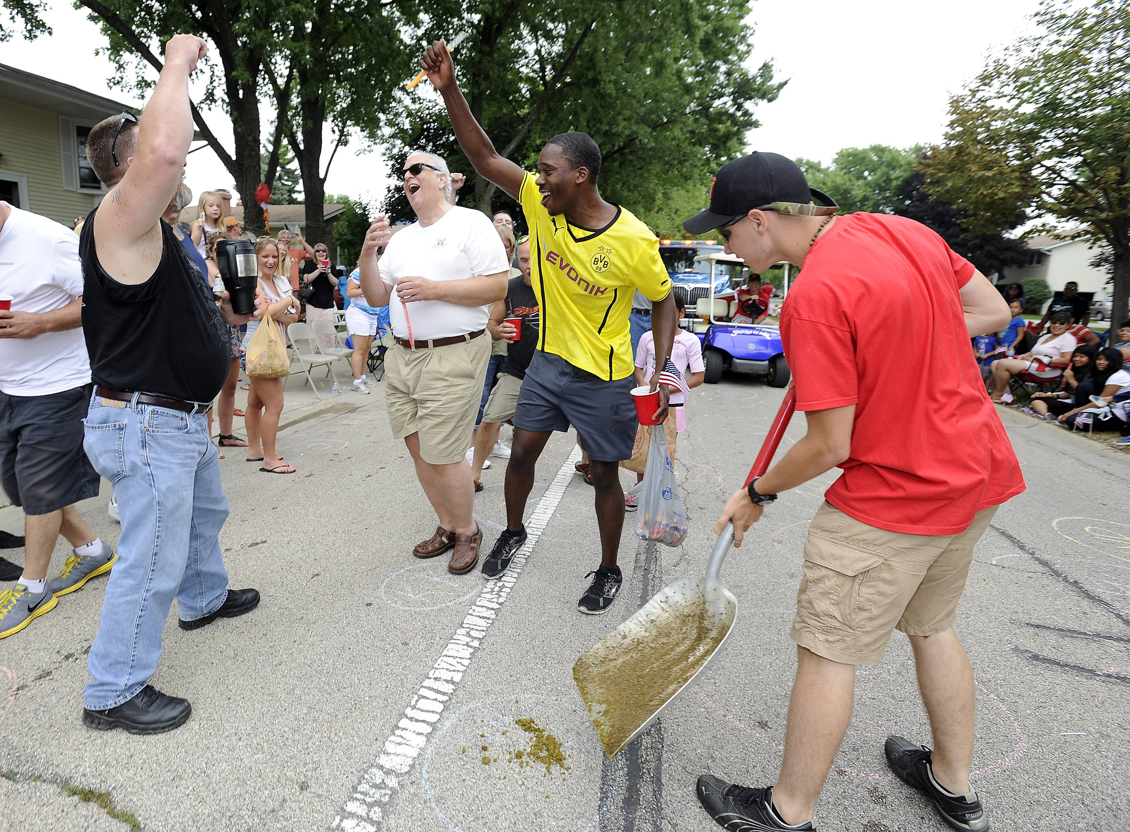 Austin Steerly of Sandwich dumps a little horse manure in the circle on the street belonging to Trez Norwood of Streamwood, center, who as a result won $73 in a friendly competition at a party held in conjunction with the parade.