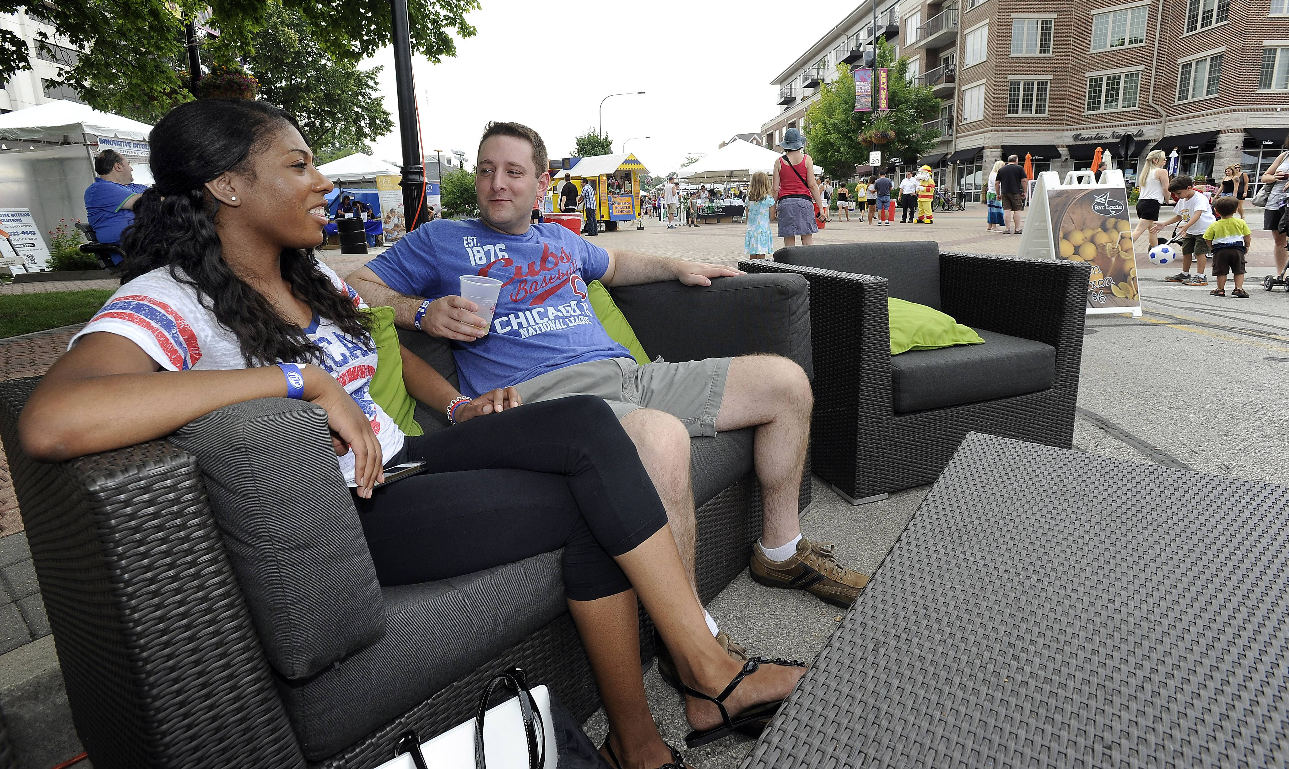 Tiffany Williams of Evanston and Shane O'Donnell of Indiana chill out with cold drinks and a front-row seat for the action Saturday at the 15th annual Mount Prospect Downtown Block Party.