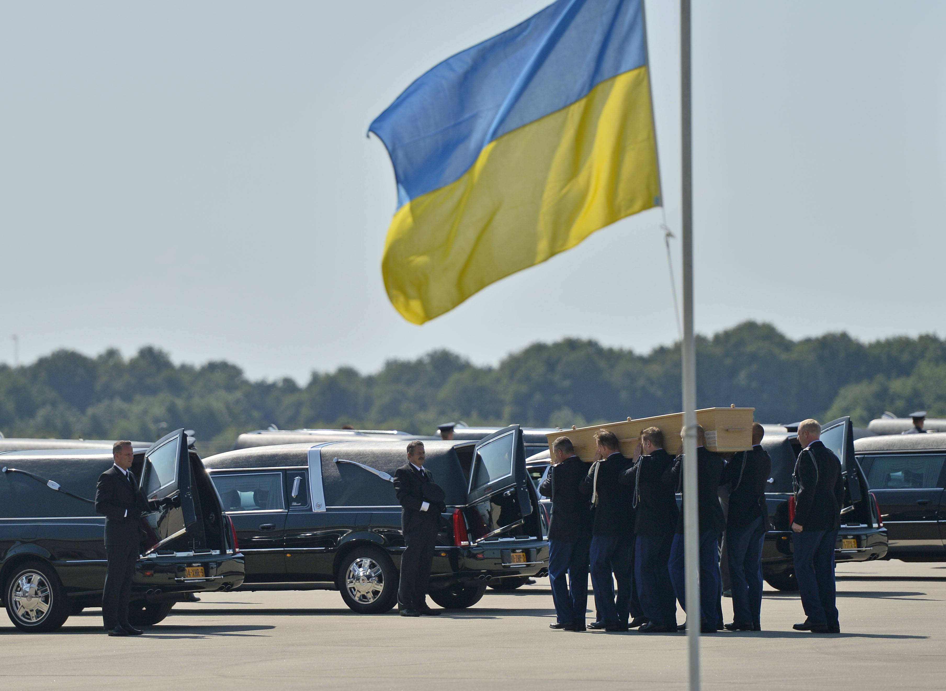 Soldiers load coffins into cars under a Ukrainian flag during a ceremony to mark the return of the first bodies, of passengers and crew killed in the downing of Malaysia Airlines Flight 17, from Ukraine at Eindhoven military air base Wednesday After being removed from the planes, the bodies are to be taken in a convoy of hearses to a military barracks in the central city of Hilversum, where forensic experts will begin the painstaking task of identifying the bodies and returning them to their loved ones.
