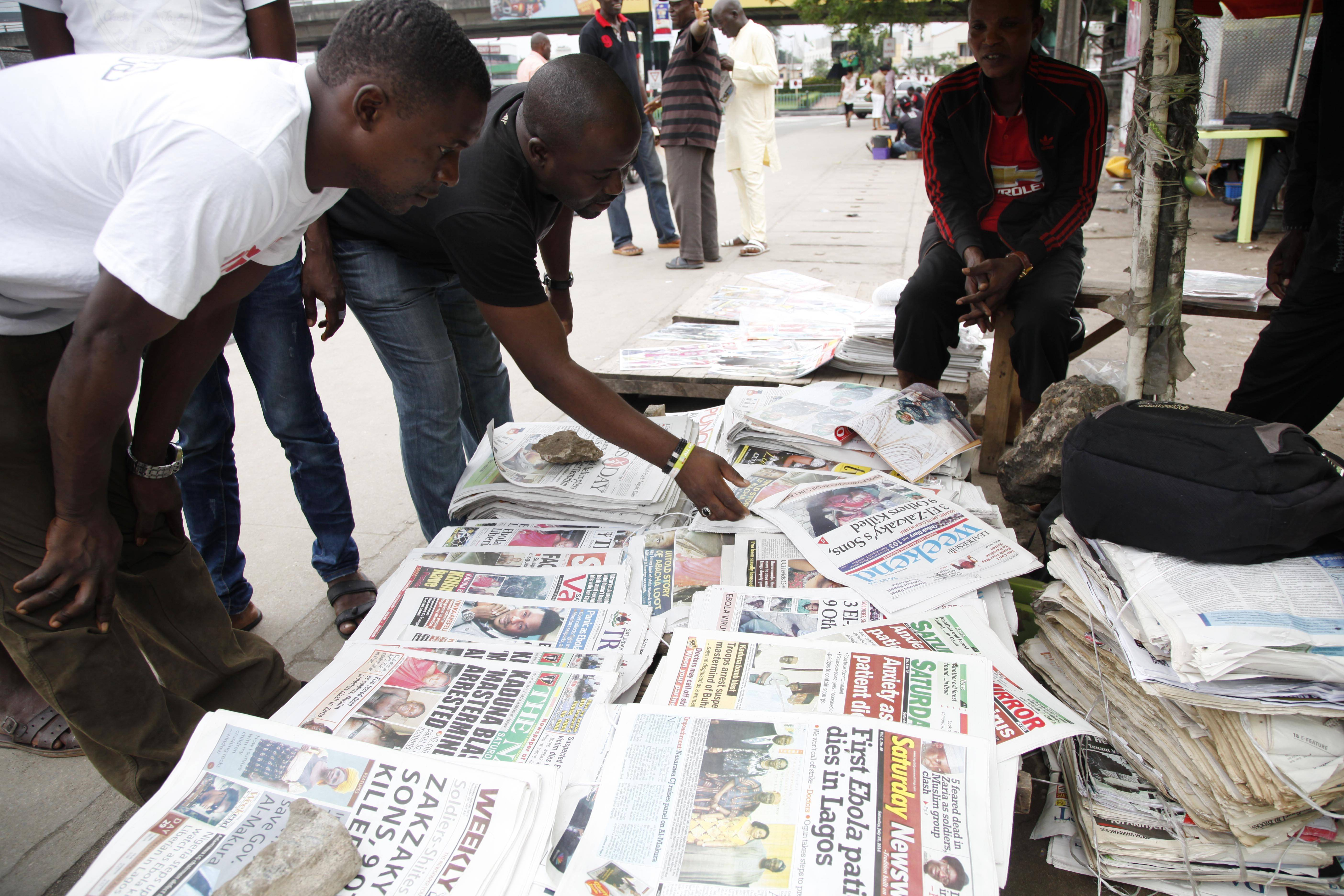 Men read newspapers Saturday on a street with headlines about Ebola Virus killing a Liberian in Lagos, Nigeria An Ebola outbreak that has left more than 660 people dead across West Africa has spread to the continent's most populous nation after a Liberian man with a high fever vomited aboard an airplane to Nigeria and then died there, officials said Friday. The 40-year-old man had recently lost his sister to Ebola in Liberia, health officials there said. It was not immediately clear how he managed to board a flight, but he was moved into an isolation ward upon arrival in Nigeria on Tuesday and died on Friday.