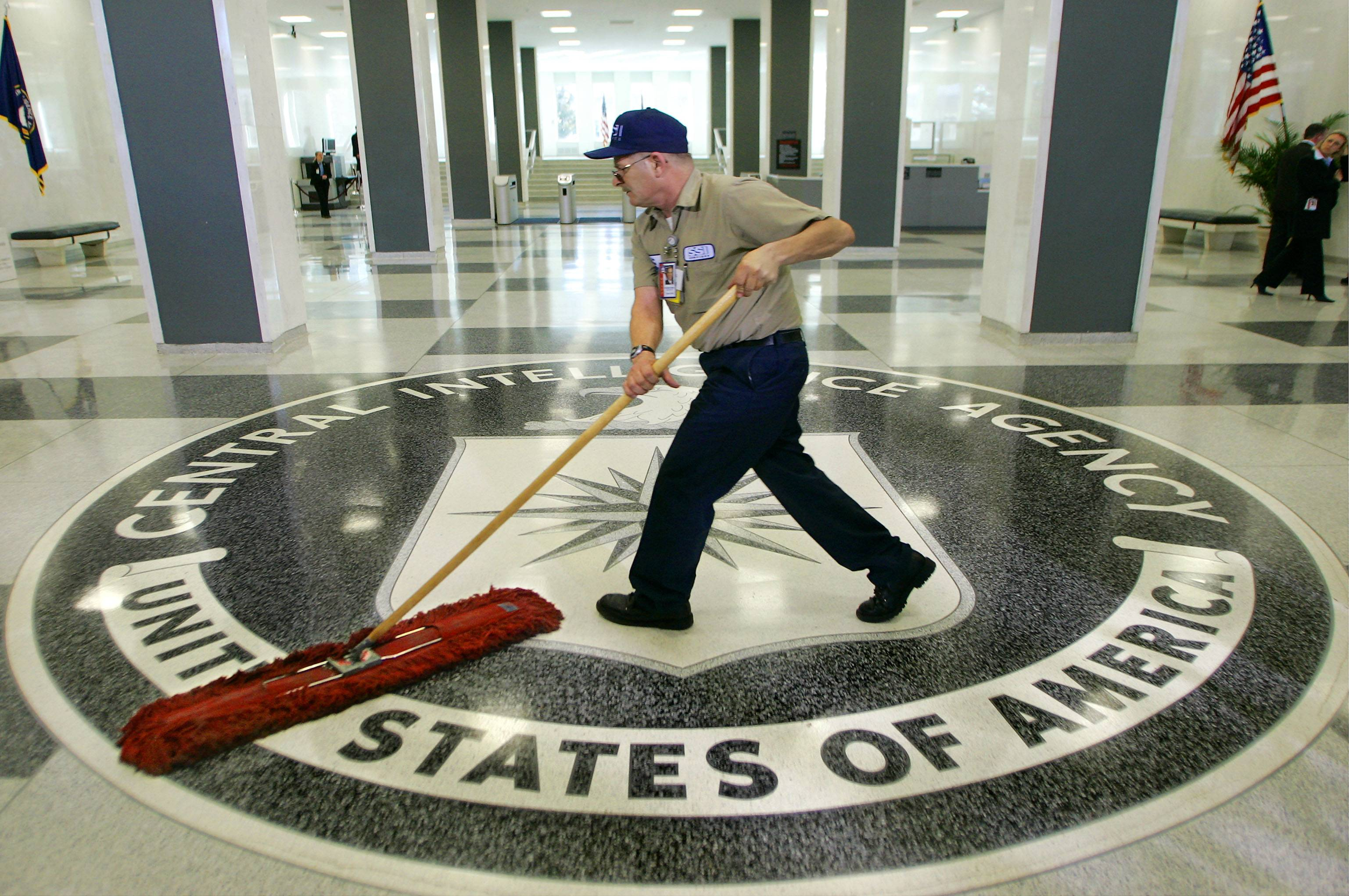 A workman quickly slides a dust mop over the floor at the Central Intelligence Agency headquarters in Langley, Va., near Washington, in this file photo. About a dozen former CIA officials named in a classified Senate report on decade-old agency interrogation practices were notified in recent days that they would be able to review parts of the document in a secure room in suburban Washington after signing a secrecy agreement. Then, on Friday, July 25, many were told they would not be able to see it, after all.